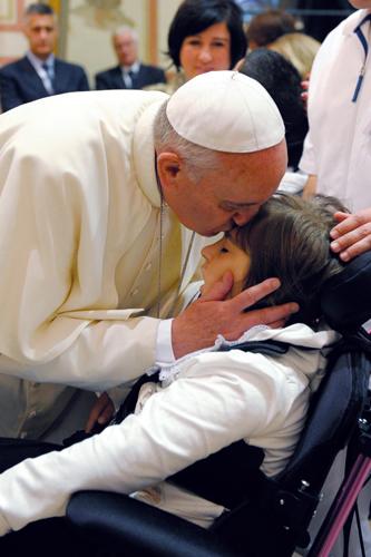 Papa Francesco bacia un bambino disabile durante la visita all'Istituto Serafico di Assisi