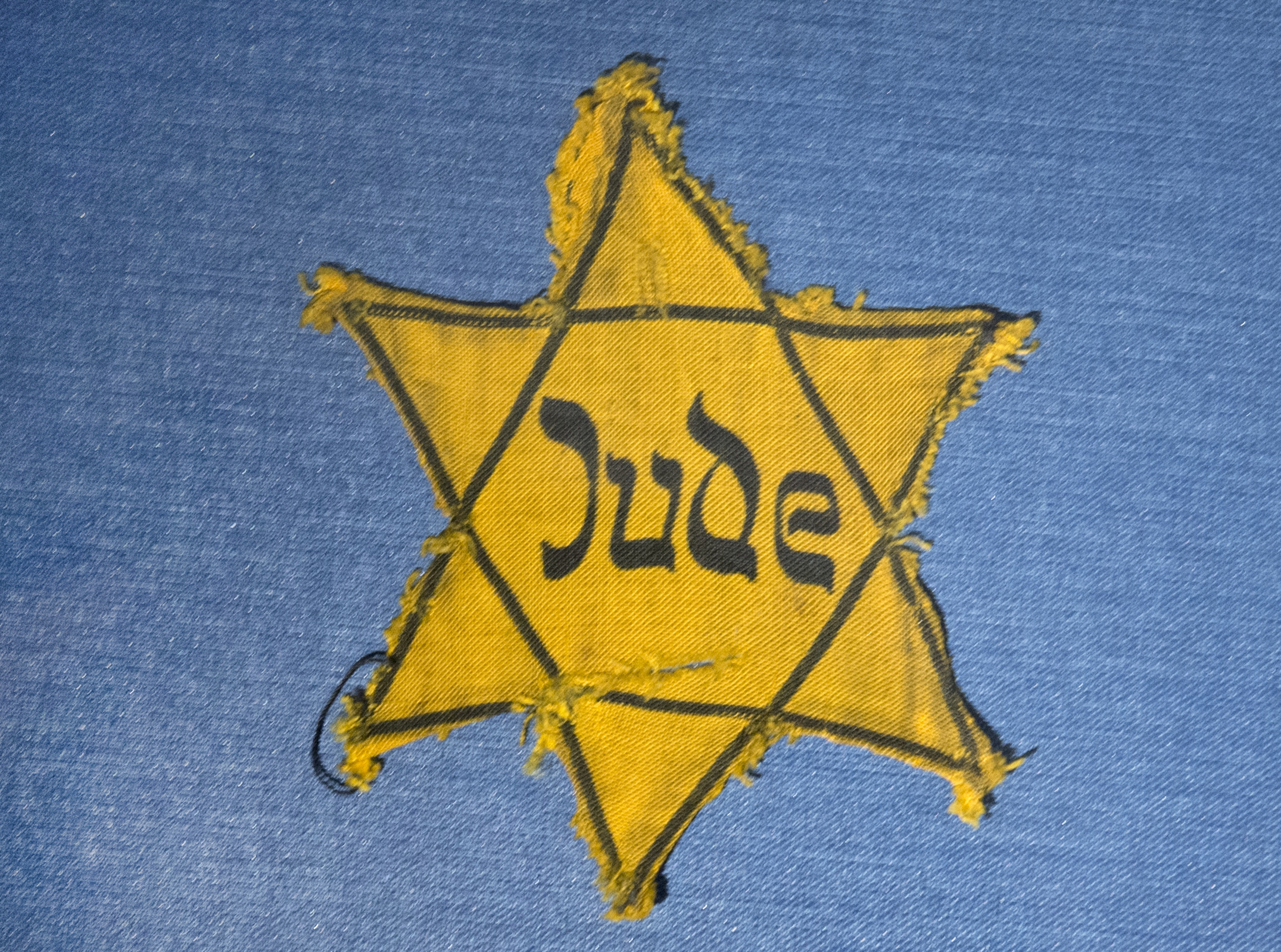 The Yellow Star badge of Heinz-Joachim Aris (Dresden 1941) reading 'Jew' is displayed  in a showcase during a press preview in the new special exhibition 'Shoes of the Dead - Dresden and the Shoah' at the Military History Museum in Dresden in Dresden, eastern Germany, Wednesday, Jan. 22, 2014.  The exhibition    is in remembrance of  Jewish citizens who were transported from  Dresden's train stations to the Nazi concentration camps. The exhibition starts on Jan. 23, 2014 and lasts until March 25, 2014.. (AP Photo/Jens Meyer)