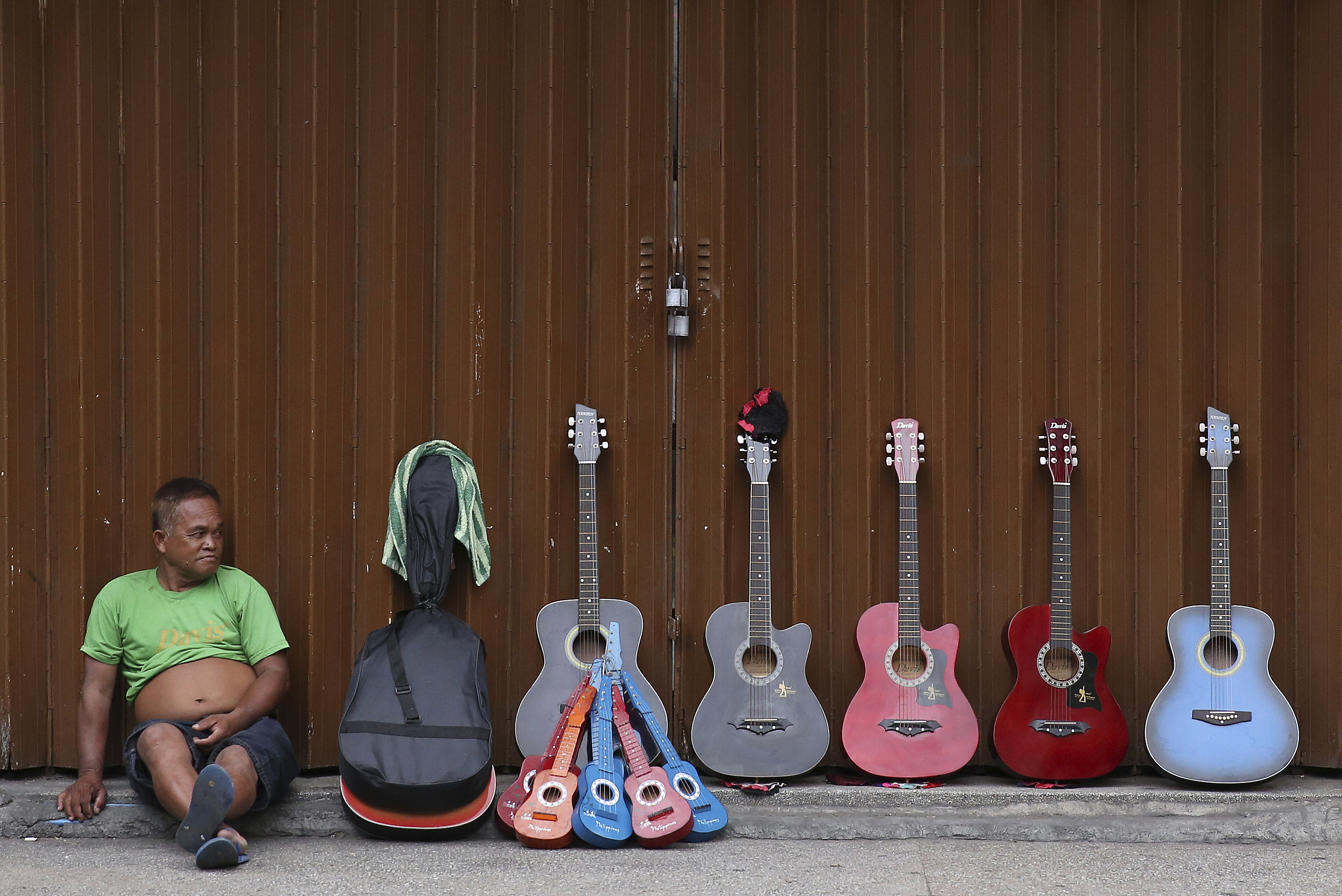 A guitar vendor Michael Hiyas, 57,  waits for customers along a street in Manila, Philippines on Thursday, May 18, 2017. Hiyas says his guitars are often bought by tourists and he earns about P400 (about US$8) a day. (AP Photo/Aaron Favila)