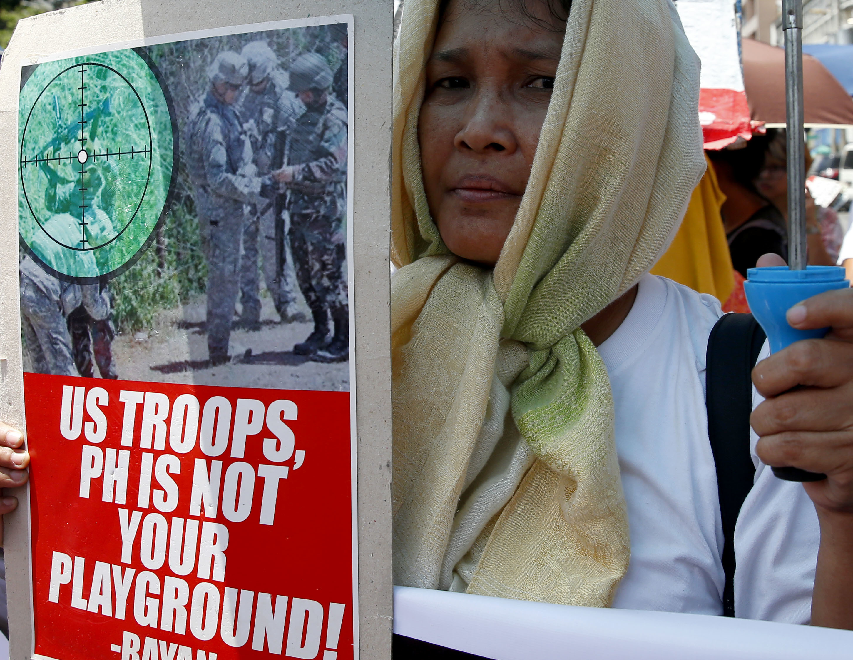 A protester holds a placard during a rally near the U.S. Embassy to denounce the U.S. military's role in the ongoing battle between Government forces and Muslim militants who laid siege to Marawi city in southern Philippines for three weeks now Monday, June 12, 2017 in Manila, Philippines. The protesters also denounced President Rodrigo Duterte's declaration of Martial Law in the whole region of Mindanao in southern Philippines.(AP Photo/Bullit Marquez)