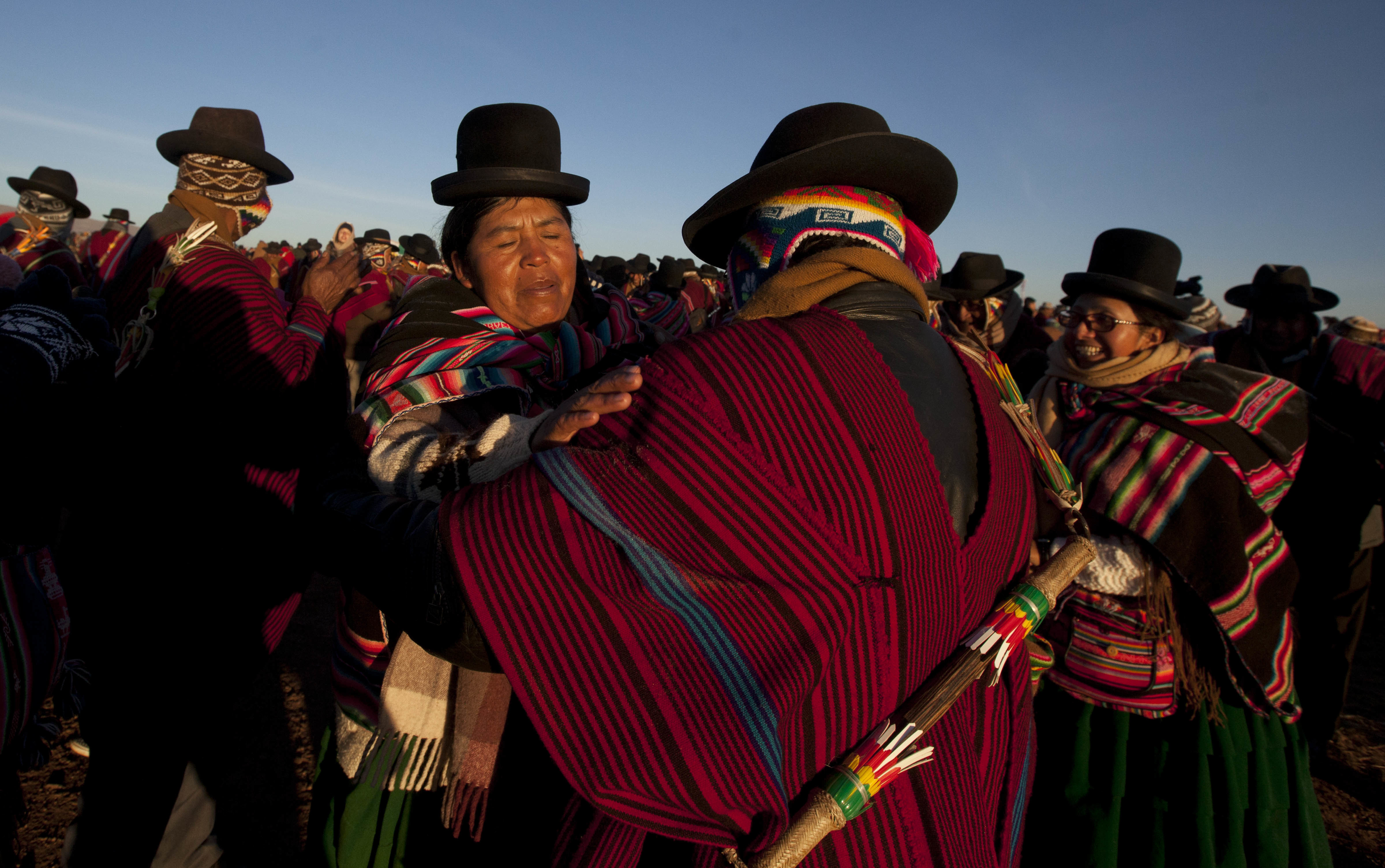 Aymara Indians embrace while receiving the first rays of sunlight in a New Year's ritual at the ruins of the ancient city Tiwanaku, Bolivia, early Wednesday, June 21, 2017. Bolivia's Aymara Indians are celebrating the year 5,525 as well as the Southern Hemisphere's winter solstice, which marks the start of a new agricultural cycle. (AP Photo/Juan Karita)