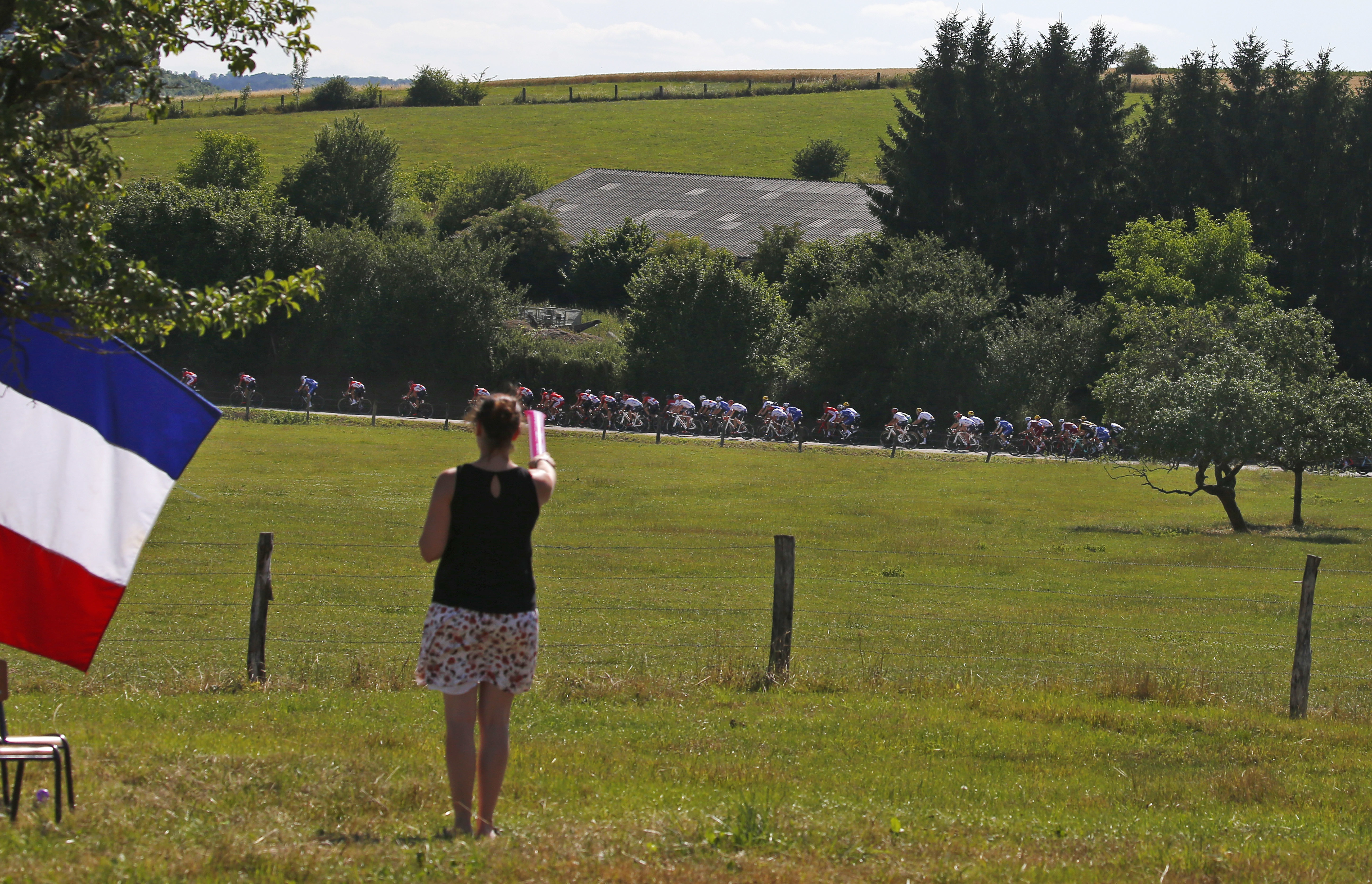 The French flag flies as a spectator points at the pack during the fourth stage of the Tour de France cycling race over 207.5 kilometers (129 miles) with start in Mondorf-les-Bains, Luxembourg, and finish in Vittel, France, Tuesday, July 4, 2017. (AP Photo/Peter Dejong)