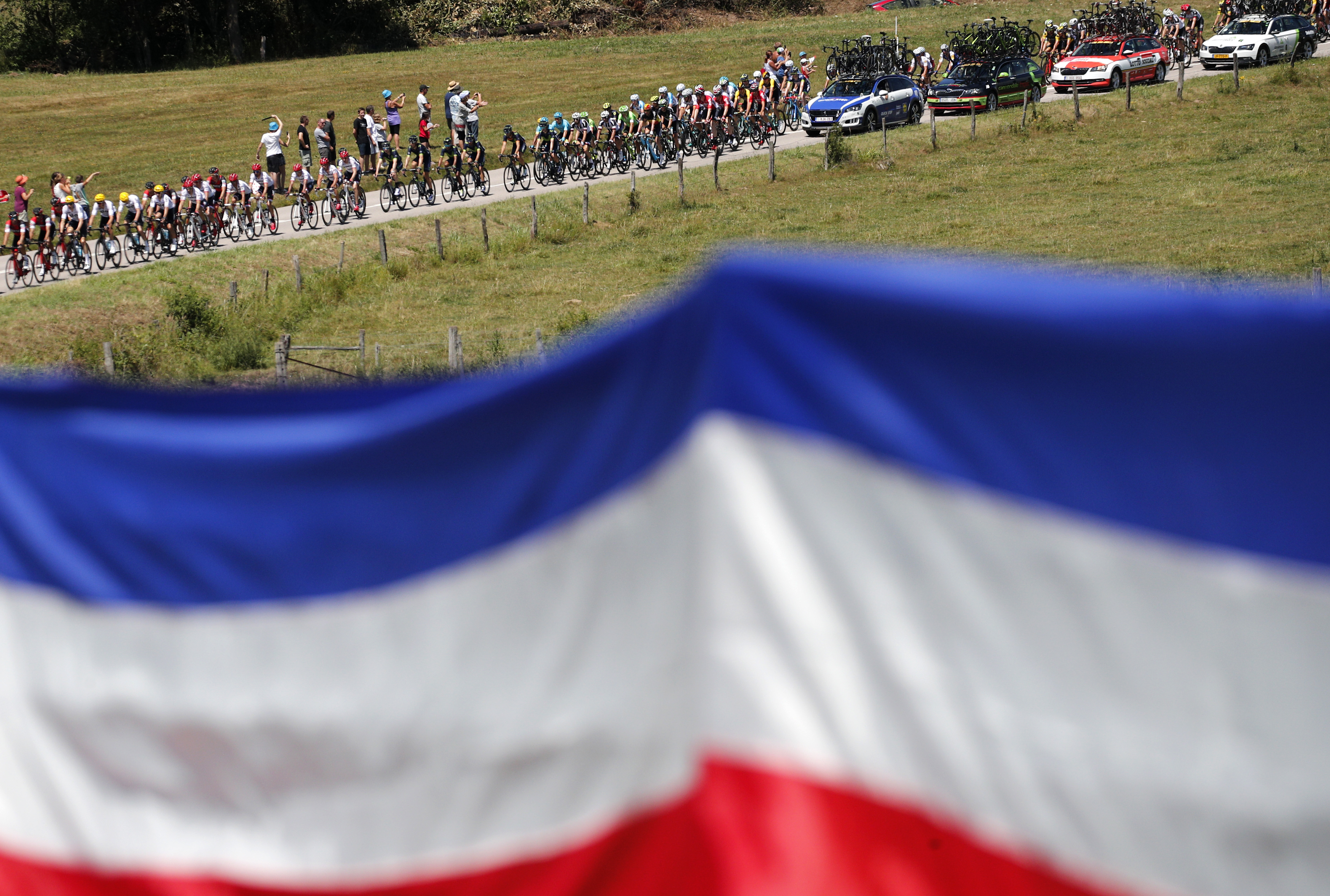 A french flag hangs from a fence as the pack approaches during the fifth stage of the Tour de France cycling race over 160.5 kilometers (99.7 miles) with start in Vittel and finish in La Planche des Belles Filles, France, Wednesday, July 5, 2017. (AP Photo/Christophe Ena)