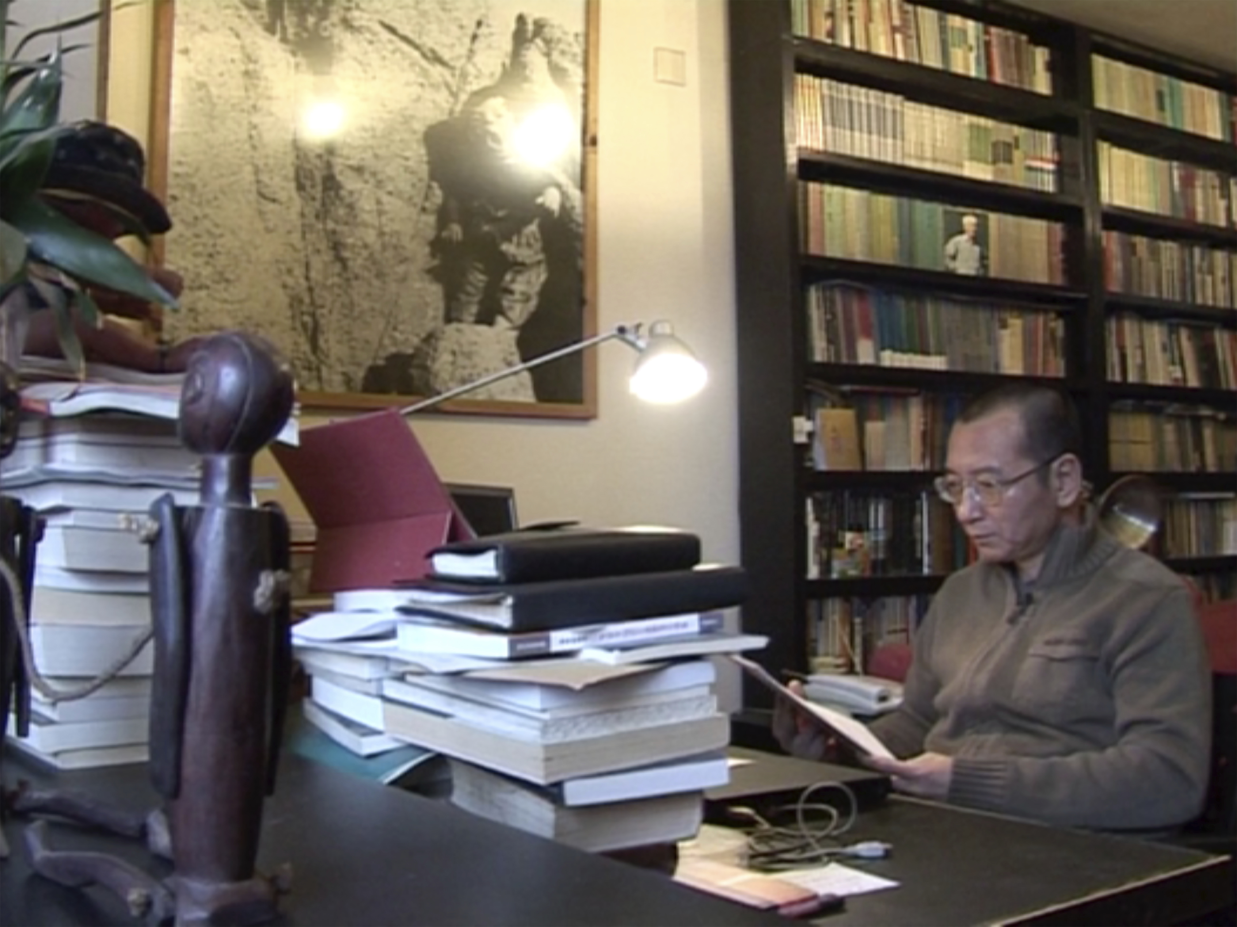 In this image taken from Jan. 6, 2008, video footage by AP Video, Liu Xiaobo looks at documents in his home in Beijing, China. At various times until his final incarceration in 2008, Liu Xiaobo's career as a lecturer, writer and literary critic intersected with China's pro-democracy movement that has been harried at every turn by the repressive powers of the one-party Communist state. (AP Video via AP)