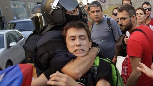 Mossos d'Esquadra regional police officer remove a protestor with an