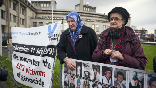 Demonstrators hold banners outside the Yugoslav War Crimes Tribunal, ICTY, where they wait for the verdict to be handed down in the genocide trial against former Bosnian Serb military chief Ratko Mladic, in The Hague, Netherlands, Wednesday Nov. 22, 2017. (AP Photo/Phil Nijhuis)