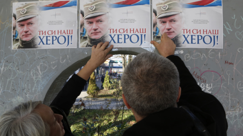 People attach posters of former Bosnian Serb military chief Ratko Mladic on a wall in Bratunac, Bosnia, Wednesday, Nov. 22, 2017. The Yugoslav War Crimes Tribunal in the The Hague is scheduled to hand down the verdict in the genocide case against former Bosnian Serb military chief Ratko Mladic on Wednesday. (AP Photo/Amel Emric)
