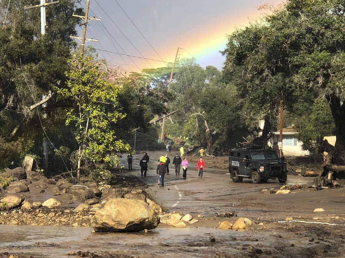 In this photo provided by Santa Barbara County Fire Department, shows a rainbow forming above Montecito, Calif. while law enforcement and the curious survey the destruction on Hot Springs Road on Tuesday, Jan. 9, 2018. Homes were swept away before dawn Tuesday when mud and debris roared into neighborhoods in Montecito from hillsides stripped of vegetation during a recent wildfire. (Mike Eliason/Santa Barbara County Fire Department via AP)