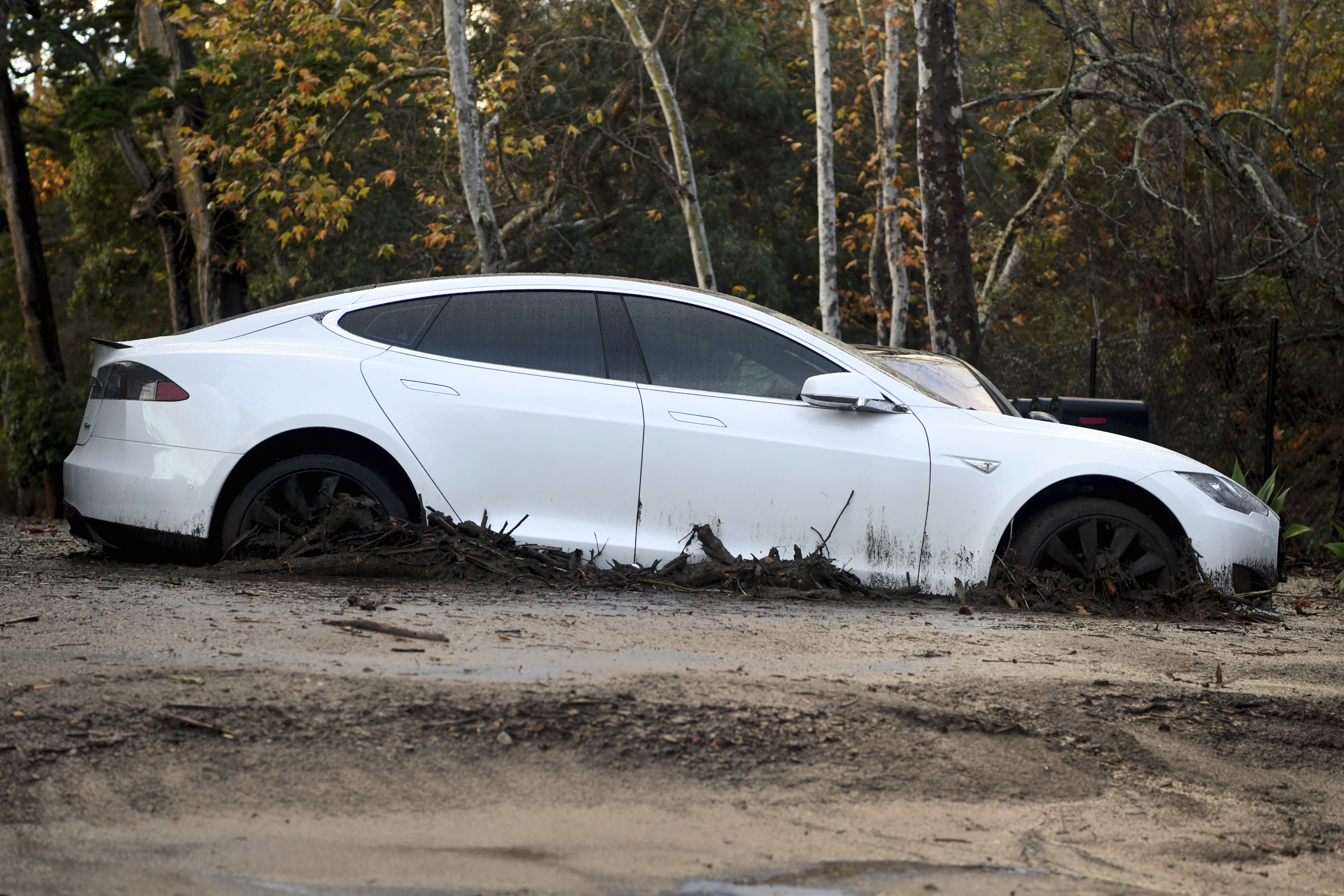 A Tesla sits in mud at a housing complex in Montecito, Calif., Tuesday, Jan. 9, 2018. Dozens of homes were swept away or heavily damaged Tuesday as downpours sent mud and boulders roaring down hills stripped of vegetation by a gigantic wildfire that raged in Southern California last month. (AP Photo/Michael Owen Baker)