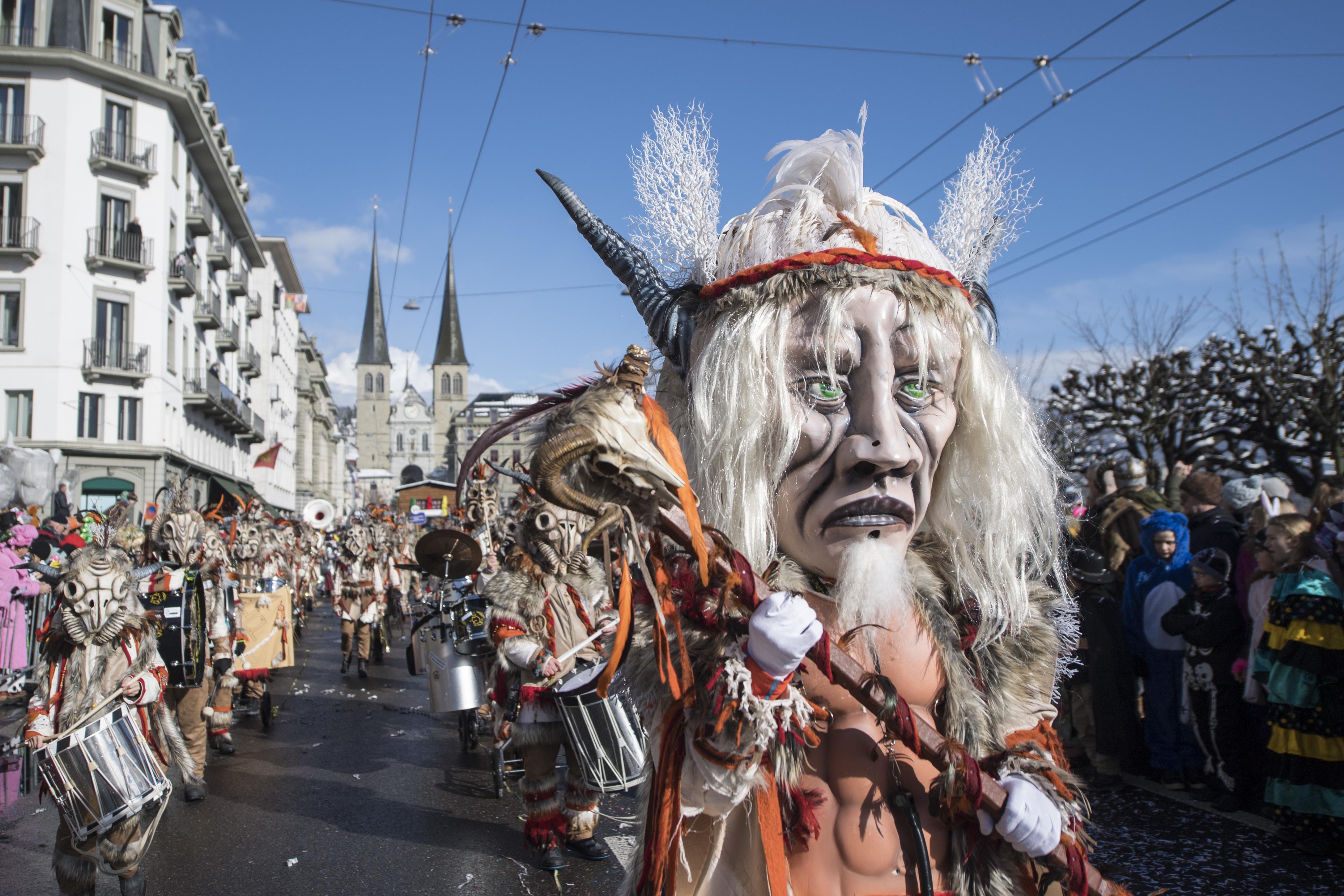 Masked revelers parade through the streets during the the carnival season in Lucerne, Switzerland, Monday, Feb. 12, 2018. (Urs Flueeler/Keystone via AP)