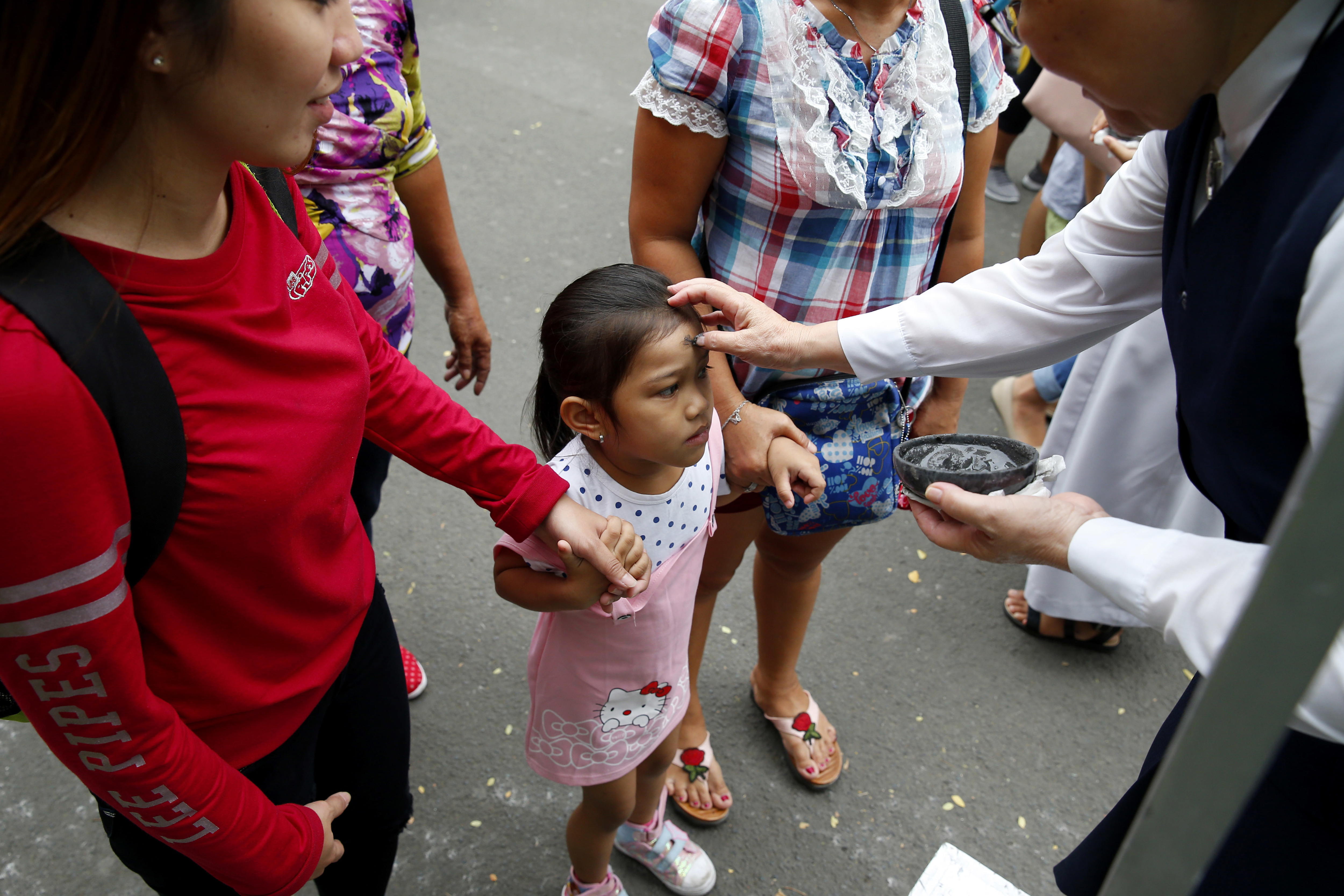A child's forehead is rubbed with ash in observance of Ash Wednesday which ushers the season of Lent and also coincides with Valentine's Day celebration Wednesday, Feb. 14, 2018, in Paranaque southeast of Manila, Philippines. Ash Wednesday is observed all over the world by Roman Catholics to remind mankind that God created humans from dust. (AP Photo/Bullit Marquez)
