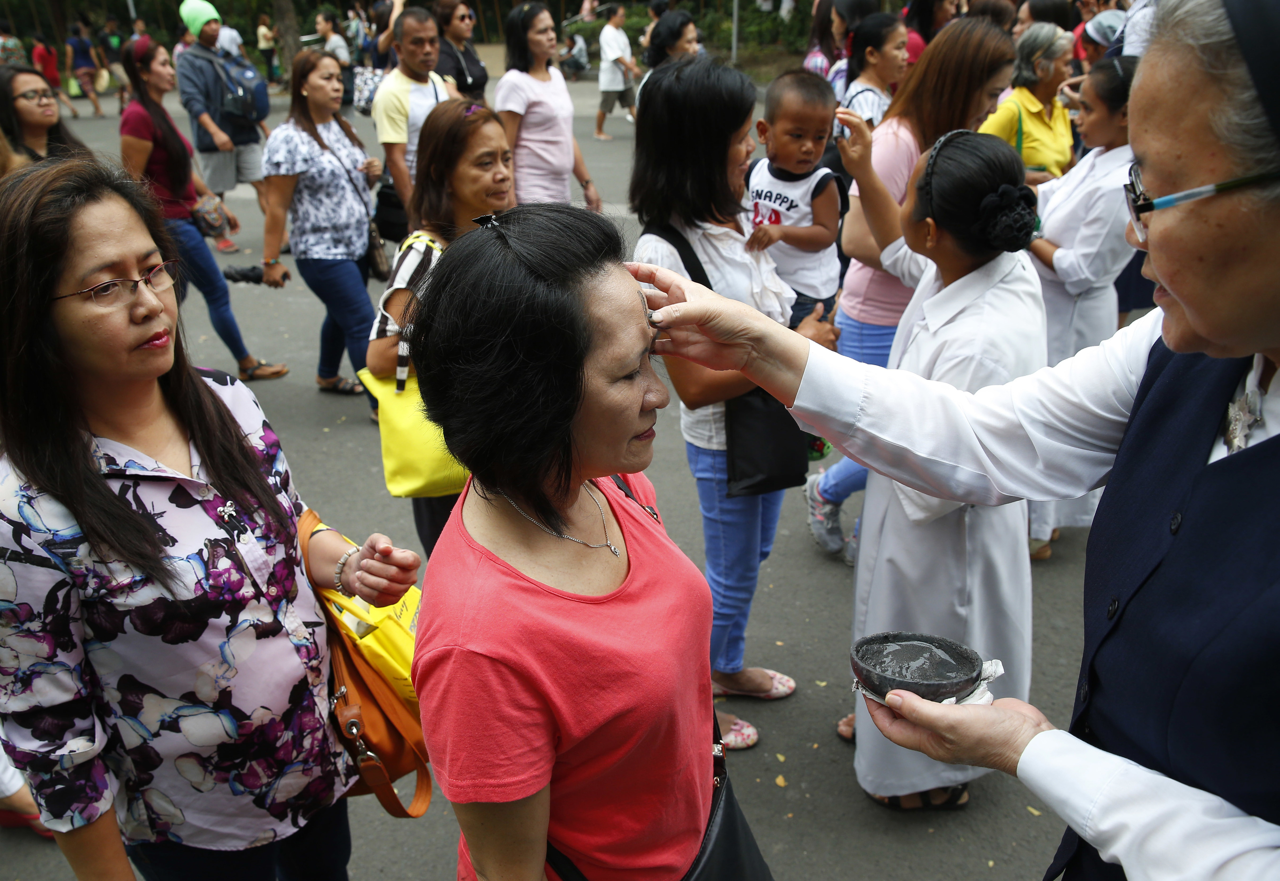Roman Catholic devotees have their foreheads rubbed with ash in observance of Ash Wednesday which ushers the season of Lent and also coincides with Valentine's Day celebration Wednesday, Feb. 14, 2018, in Paranaque southeast of Manila, Philippines. Ash Wednesday is observed all over the world by Roman Catholics to remind mankind that God created humans from dust. (AP Photo/Bullit Marquez)