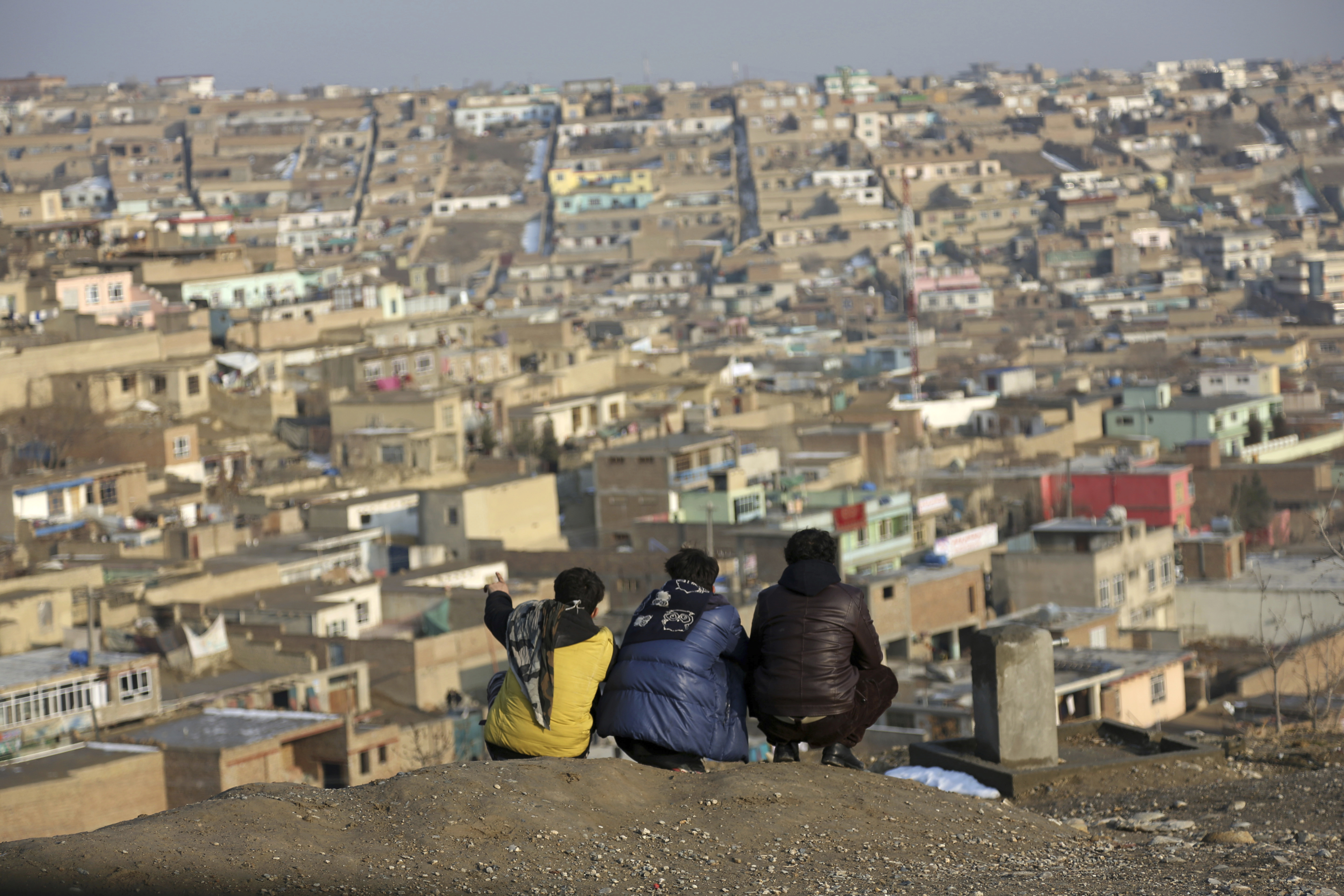 Afghan boys look over the city of Kabul, Afghanistan, Tuesday, Jan. 30, 2018. (AP Photo/Rahmat Gul)