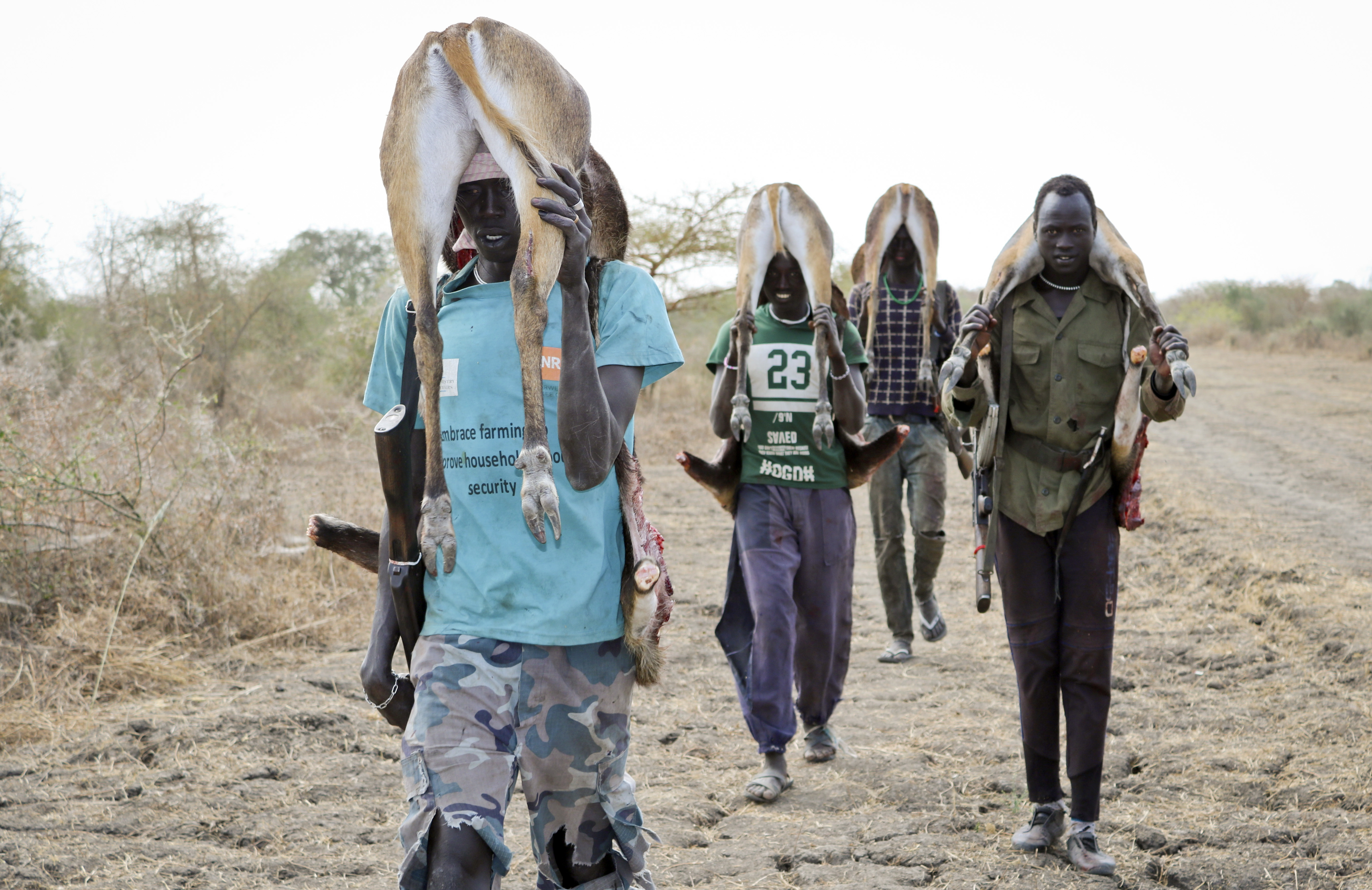 In this photo taken Wednesday, Jan. 24, 2018, men return from the bush after hunting gazelle to sell at the market in Akobo town, one of the last rebel-held strongholds in South Sudan. South Sudan's opposition is threatening to resort to