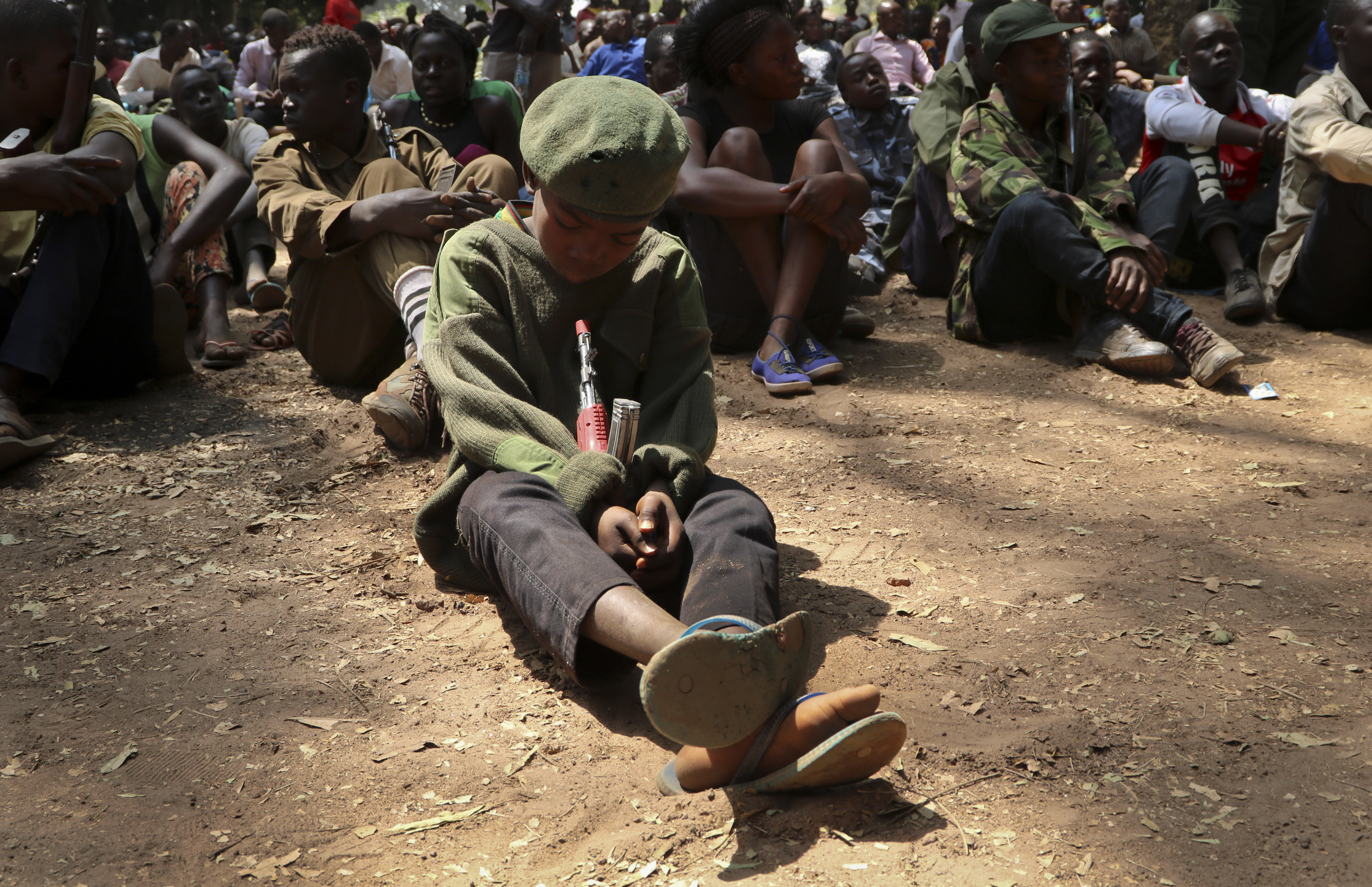 A young child soldier sits on the ground at a release ceremony, where he and others laid down their weapons and traded in their uniforms to return to