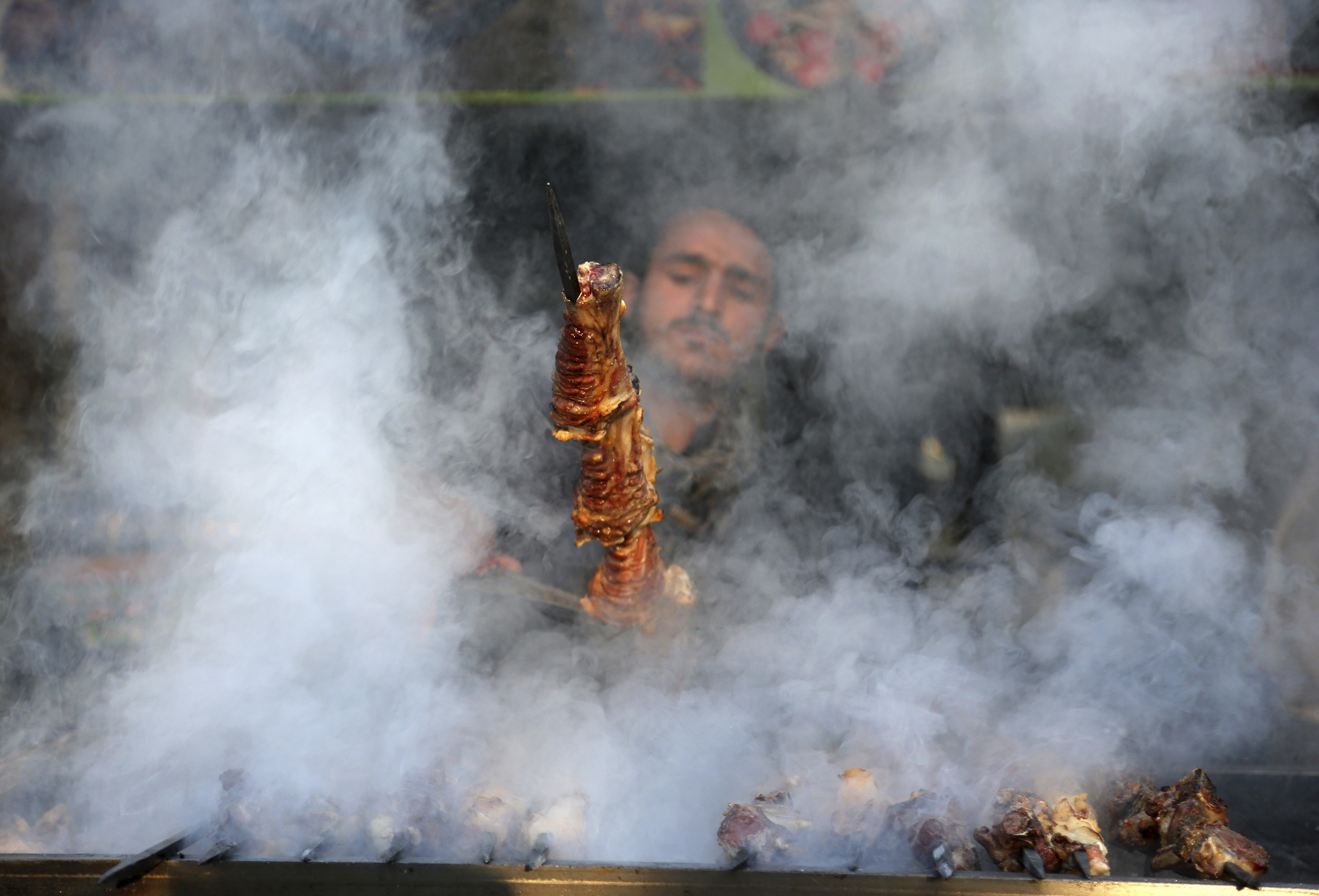 An Afghan man cooks Kabab at a restaurant in Kabul, Thursday, Feb. 8, 2018. (AP Photo/Rahmat Gul)
