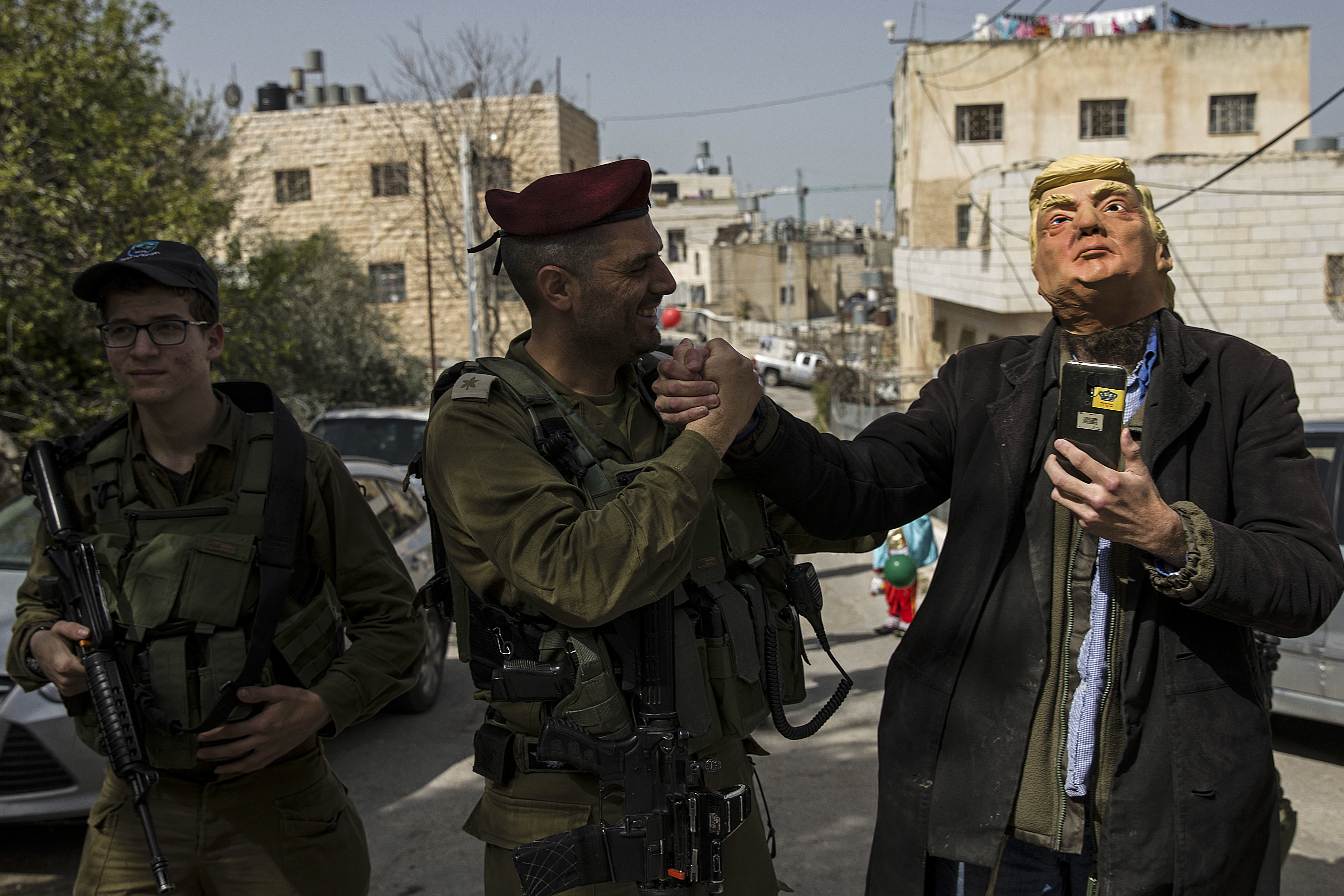 A Jewish settler wearing a U.S. President Donald Trump mask shakes hands with an  Israeli soldier as he participates in the annual parade marking the Jewish holiday of Purim, in Hebron, Thursday, March 1, 2018. The festival of Purim commemorates the rescue of Jews from genocide in ancient Persia. (AP Photo/Tsafrir Abayov)