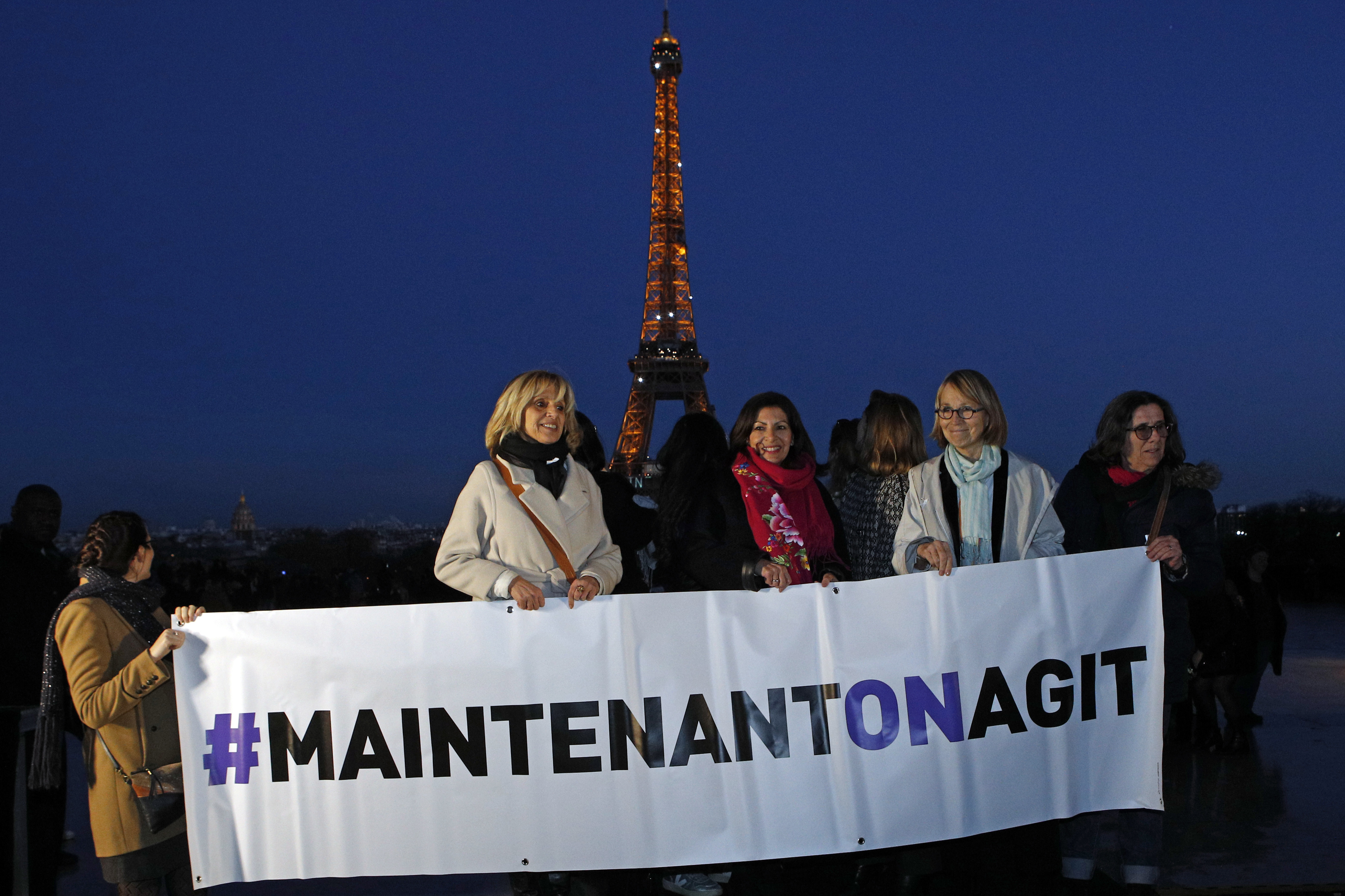 French Culture Minister Francoise Nyssen, second right, Paris mayor Anne Hidalgo, center, and members of several women's rights associations hold a banner reading