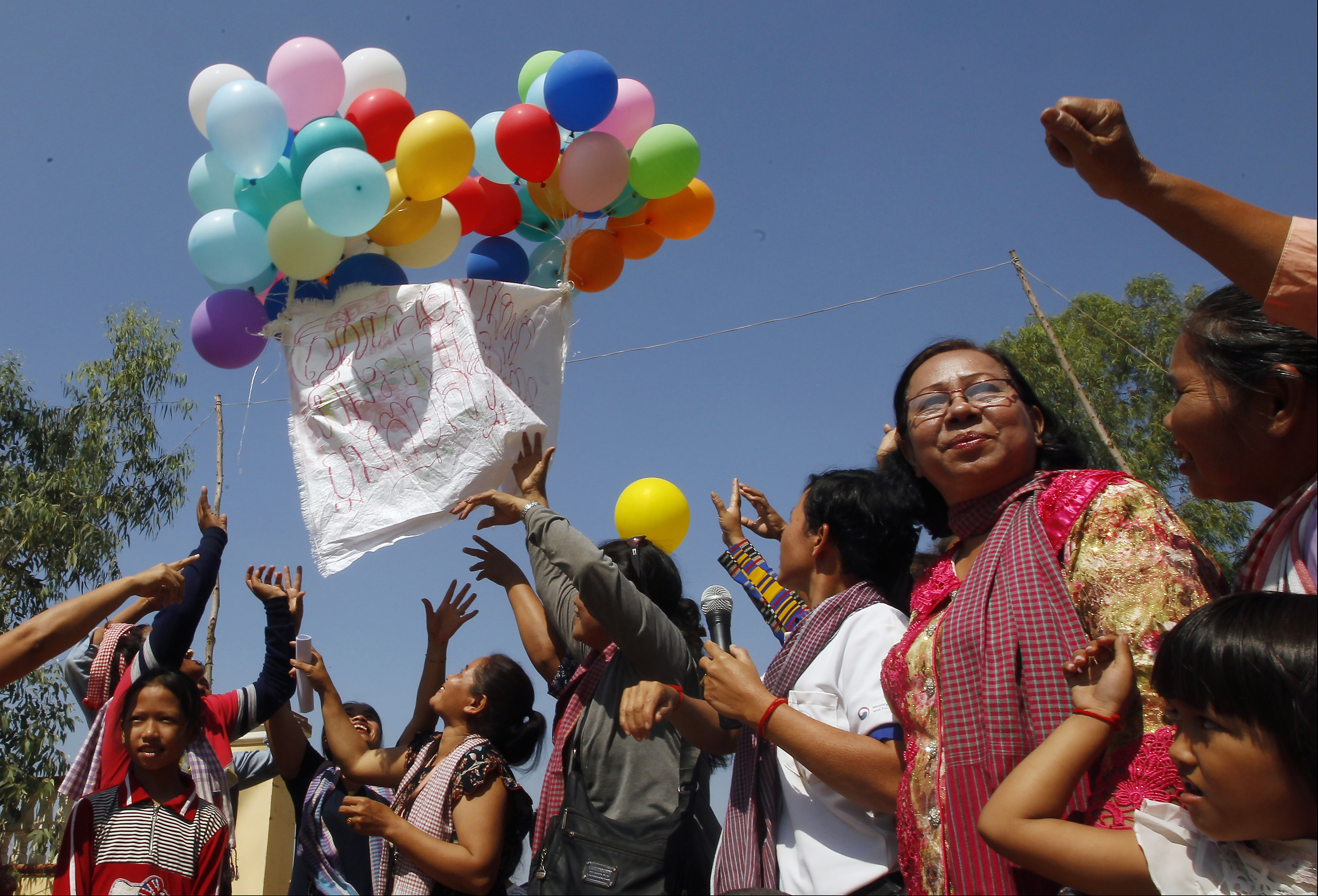 Land activists from Boeung Chhuk community release balloons to mark International Women's Day on the outskirts of Phnom Penh, Cambodia, Thursday, March 8, 2018. The community people took part in the International Women's Day celebration, coincided with the 10th anniversary of their forced eviction. (AP Photo/Heng Sinith)