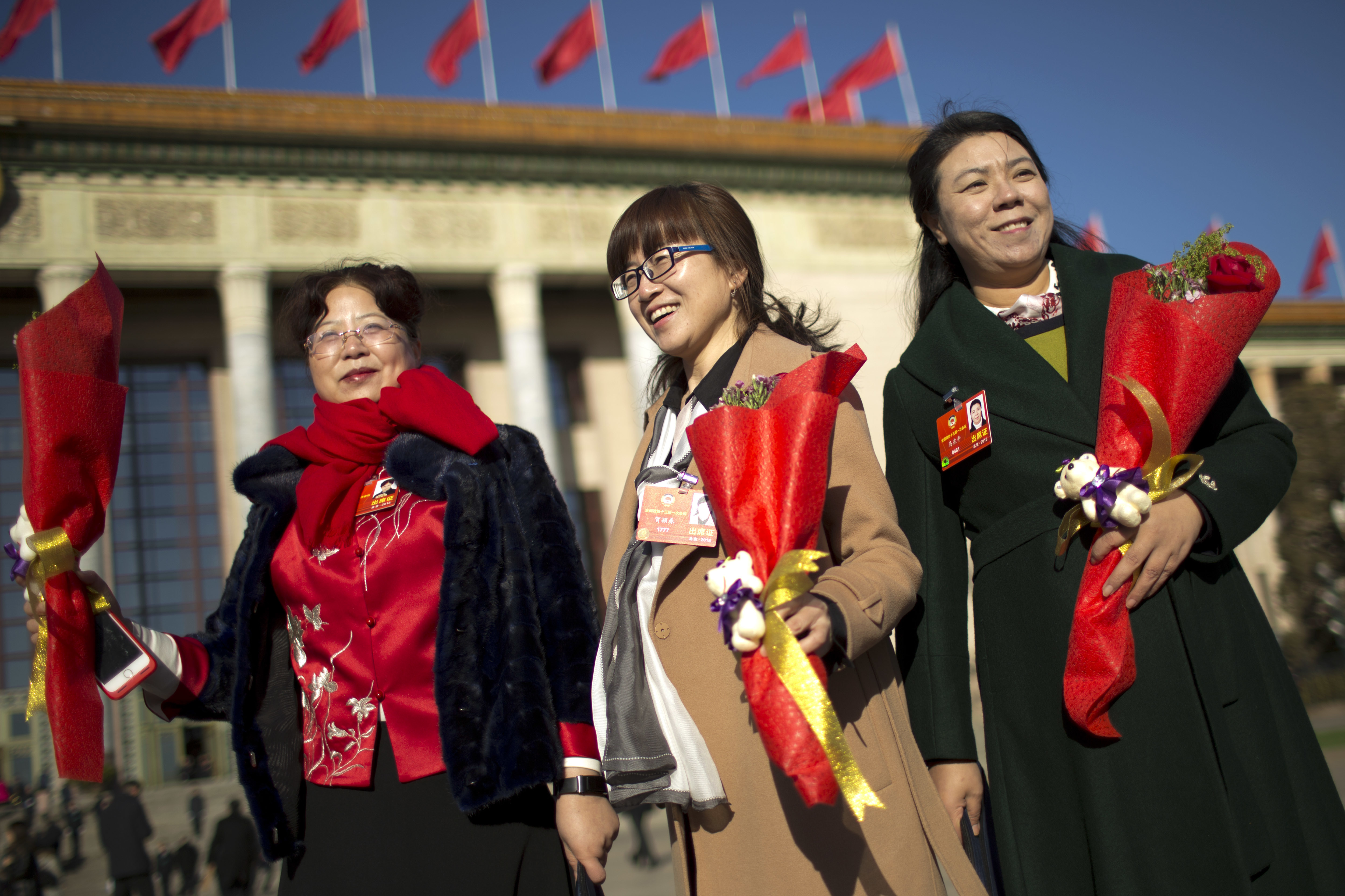 Delegates hold flower bouquets for International Women's Day as they arrive for a plenary session of the Chinese People's Political Consultative Conference (CPPCC) at the Great Hall of the People in Beijing, Thursday, March 8, 2018. Students at China's prestigious Tsinghua University are celebrating International Women's Day with banners making light of a proposed constitutional amendment to scrap term limits for the country's president. (AP Photo/Mark Schiefelbein)