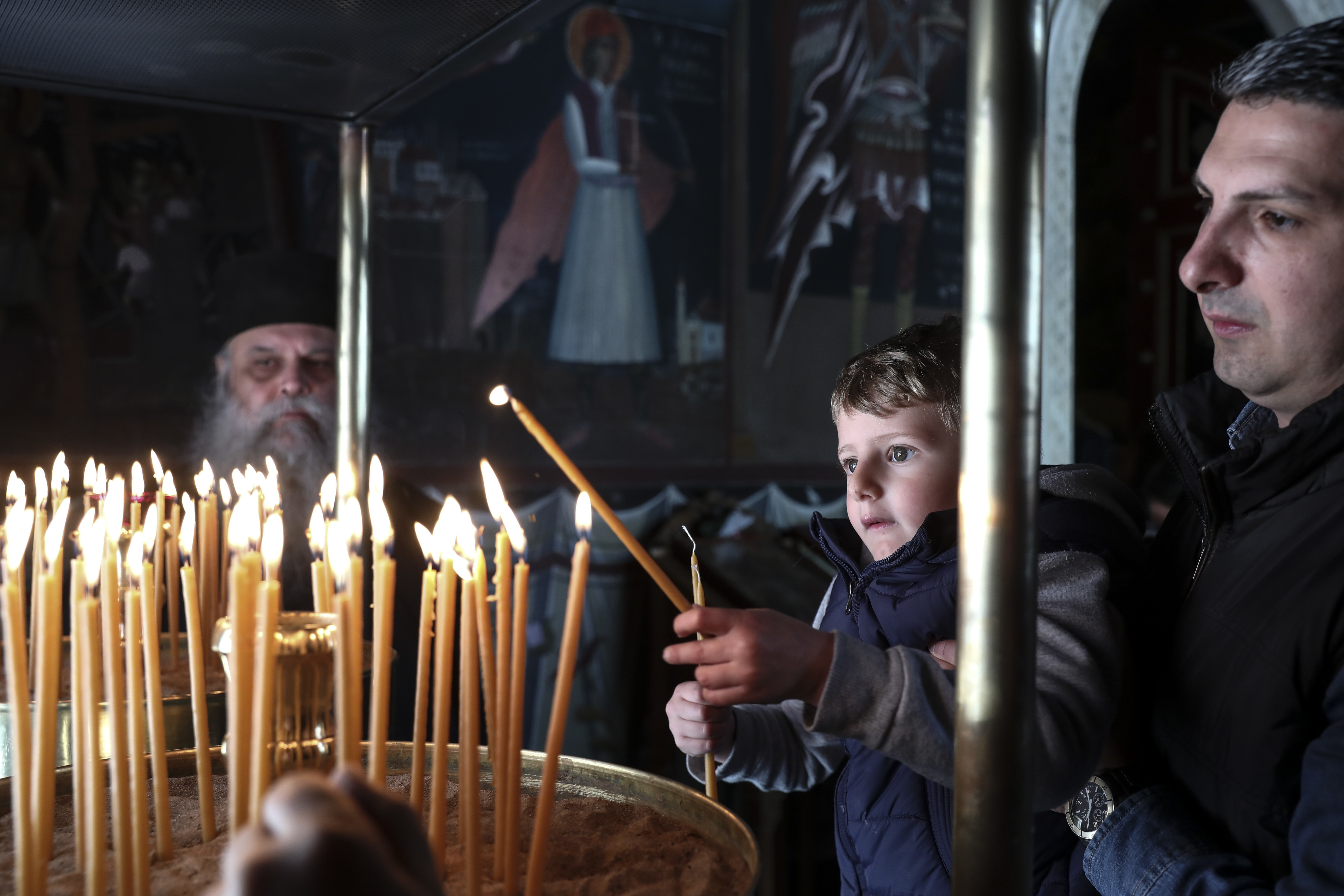A boy lights a candle during a Good Friday Mass, at the Pendeli Monastery, near Athens, on Friday, April 6, 2018. Orthodox Christians around the world celebrate Easter on Sunday, April 8. (AP Photo/Yorgos Karahalis)