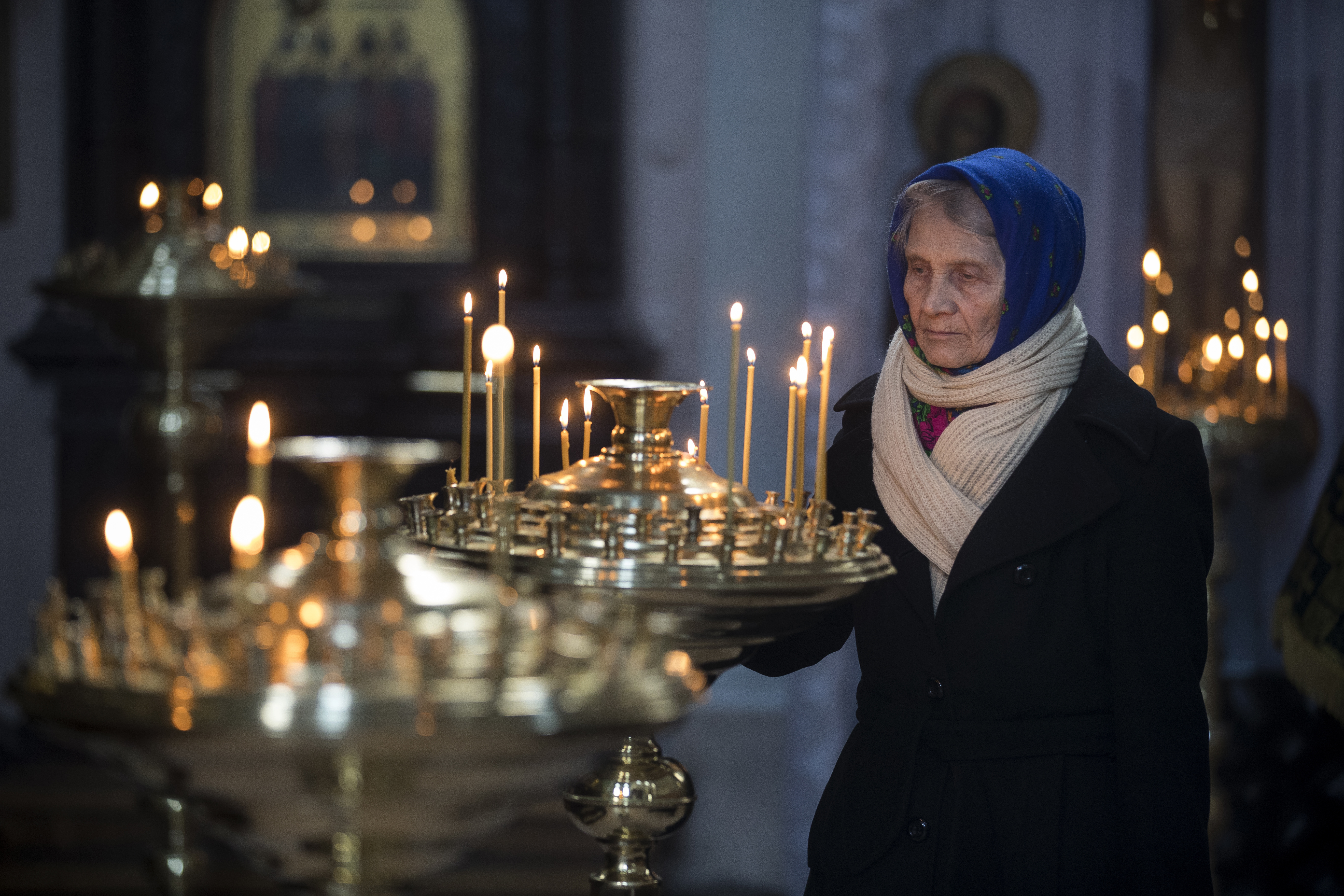 A woman lights a candle during a Good Friday Mass, at the Prechistensky, the Cathedral Palace in Vilnius, Lithuania, Friday, April 6, 2018. Orthodox Christians around the world celebrate Easter on Sunday, April 8.(AP Photo/Mindaugas Kulbis)