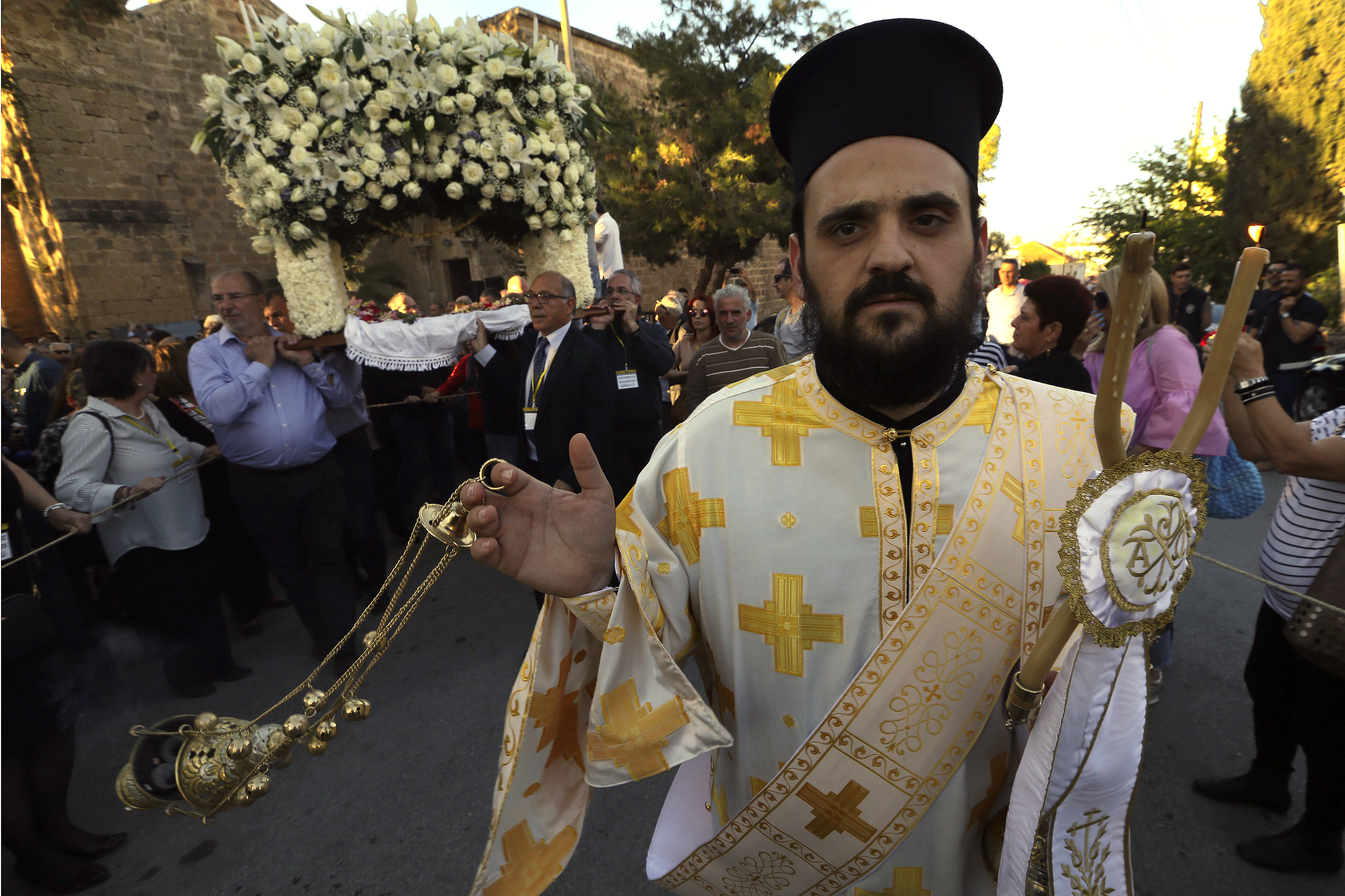 A Greek Orthodox Christian Priest holds candles during the Good Friday procession of the Epitaphios, at the church of Saint George Exorinos within the ancient walls of Famagusta city, Cyprus, on Friday, April 6, 2018. According to Orthodox tradition, the faithful follow the Epitaphios which rests under a flower-adorned canopy in procession around the church to commemorate Christ's funeral procession. This is one of the few times in recent years where Turkish Cypriot authorities have permitted liturgical services at the 14th Century church since the island was divided in 1974 when Turkey invaded following a coup by supporters of union with Greece. (AP Photo/Petros Karadjias)