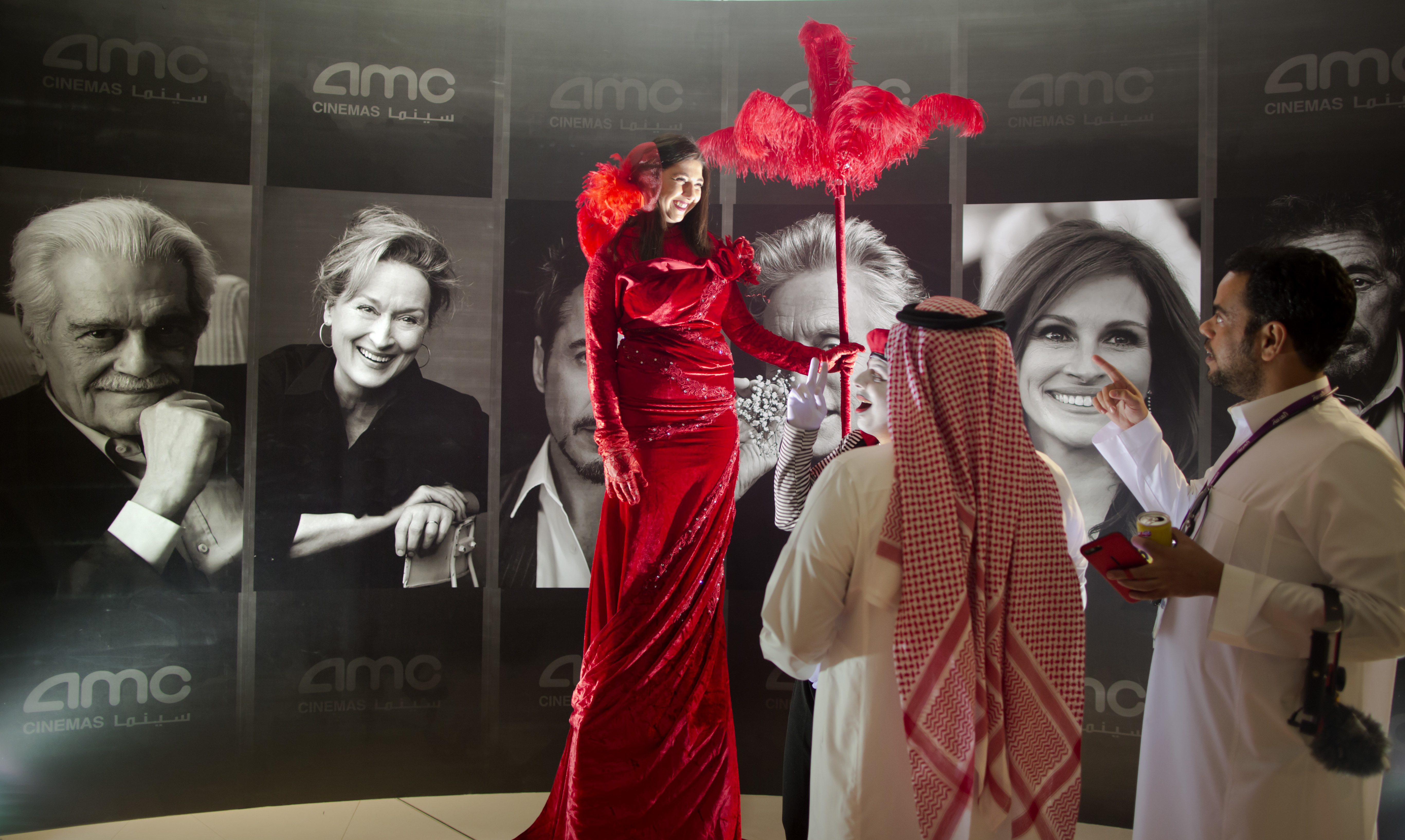Visitors chat with an actress dress with red carpet colors in front of posters of Hollywood stars during invitation-only screening, at the King Abdullah Financial District Theater, in Riyadh, Saudi Arabia, Wednesday, April 18, 2018. Saudi Arabia held a private screening of the Hollywood blockbuster