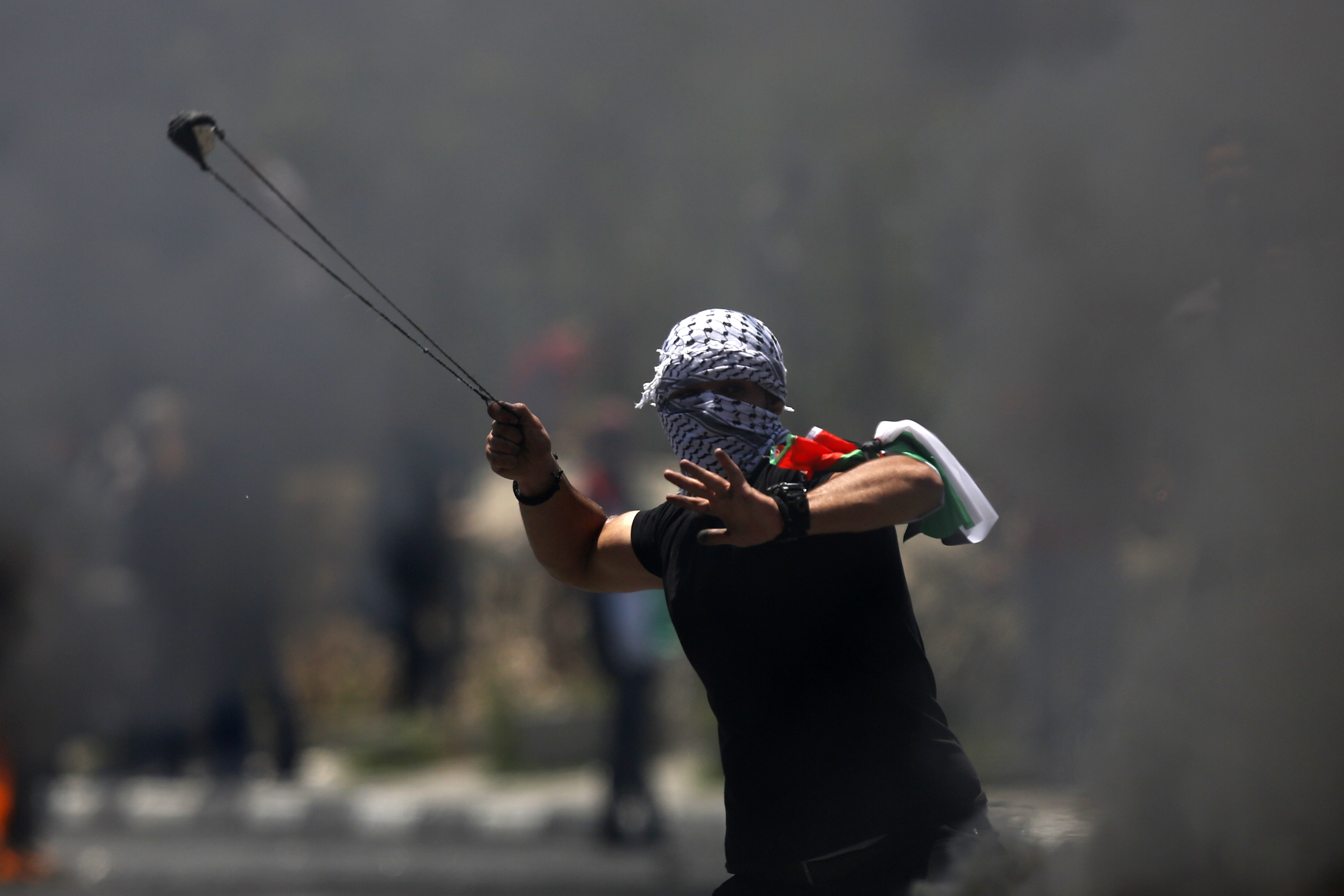 A Palestinian protester hurls a stone during clashes with Israeli forces after a rally to mark the 70th anniversary of what Palestinians call their