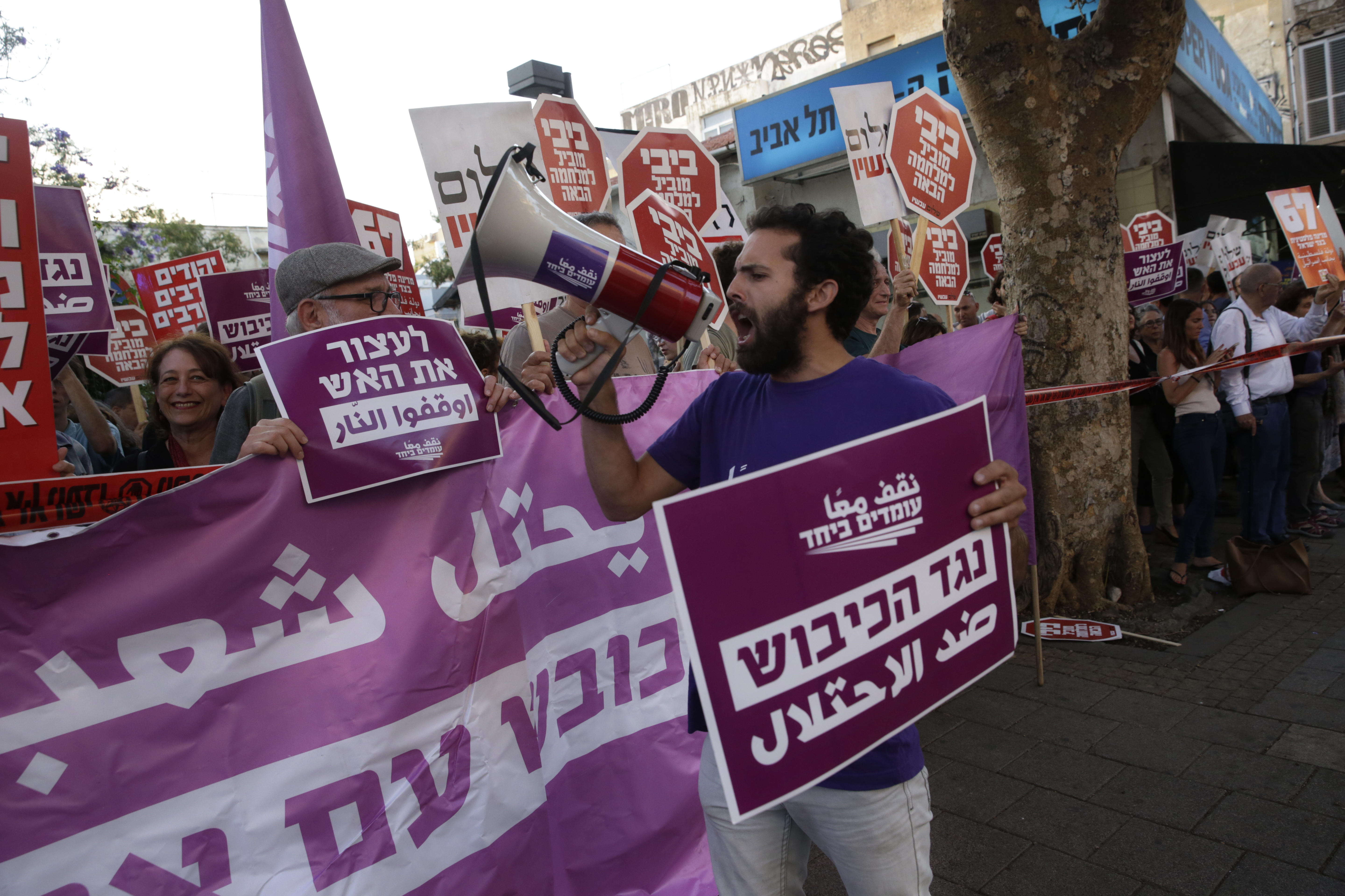Left-wing Israelis hold signs during a demonstration against the situation in Gaza in Tel Aviv, Israel, Tuesday, May 15, 2018. Israel faced a growing backlash Tuesday and new charges of using excessive force, a day after Israeli troops firing from across a border fence killed 59 Palestinians and wounded more than 2,700 at a mass protest in Gaza. Hebrew signs read: