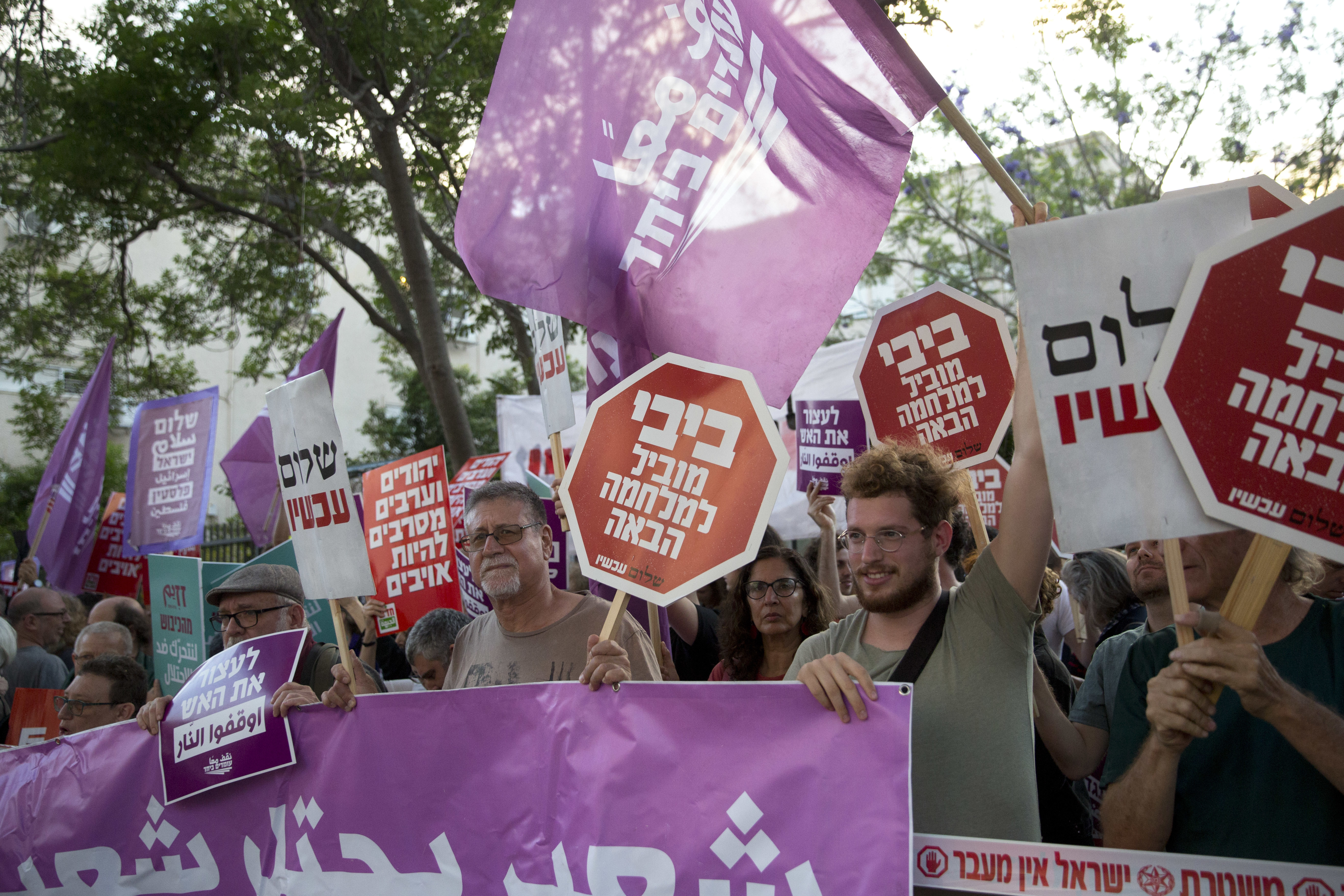 Left-wing Israelis hold signs during a demonstration against the situation in Gaza in Tel Aviv, Israel, Tuesday, May 15, 2018. Israel faced a growing backlash Tuesday and new charges of using excessive force, a day after Israeli troops firing from across a border fence killed 59 Palestinians and wounded more than 2,700 at a mass protest in Gaza. Hebrew sign reads: