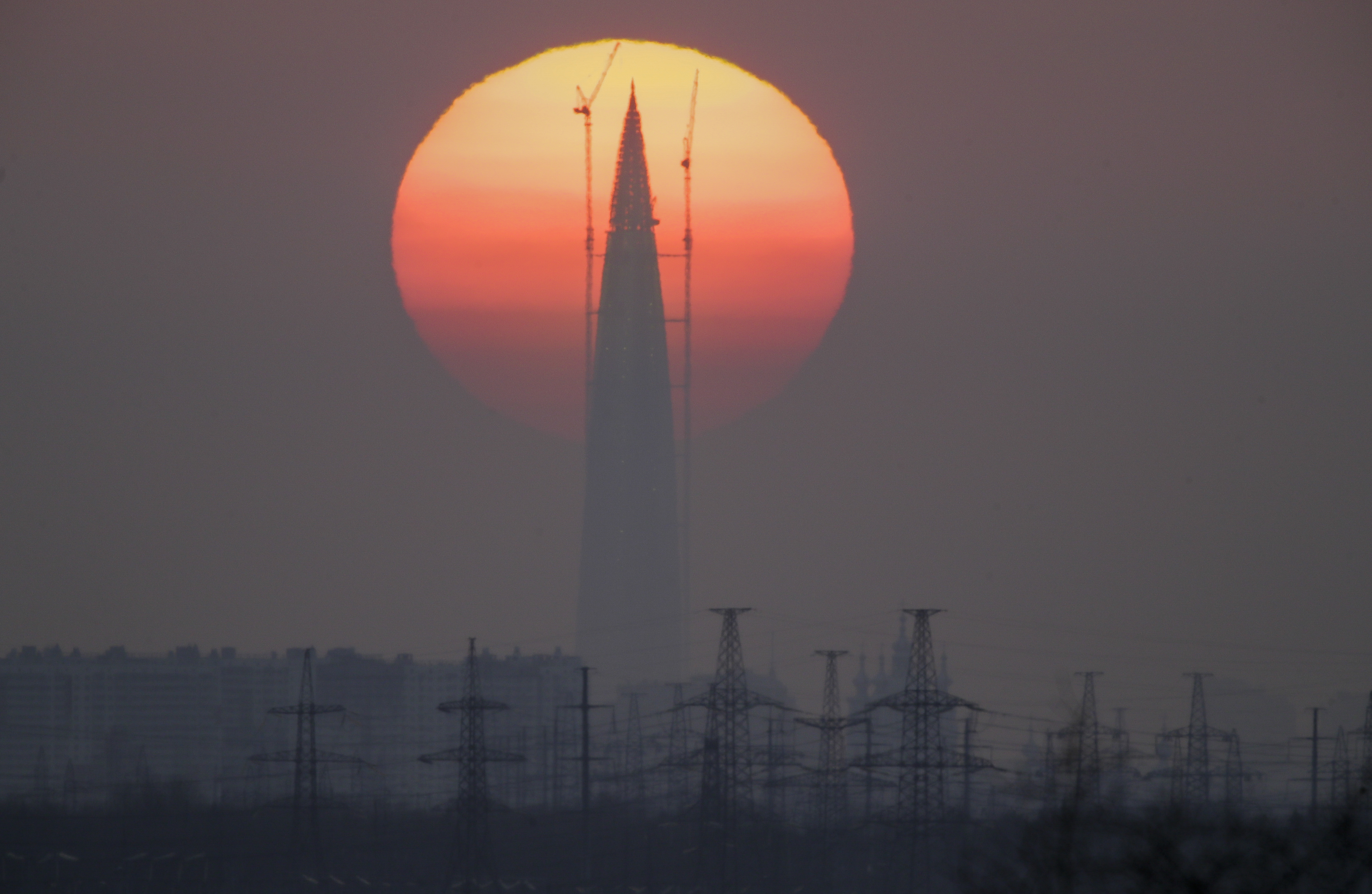 Business tower Lakhta Centre under construction, the headquarters of Russian gas monopoly Gazprom, is silhouetted against the sunset in St. Petersburg, Russia, Sunday, April 15, 2018. (AP Photo/Dmitri Lovetsky)