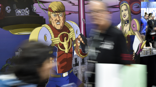 Attendees walk past cut-out figures of President Donald Trump and his daughter Ivanka at a booth for the satirical comic book series