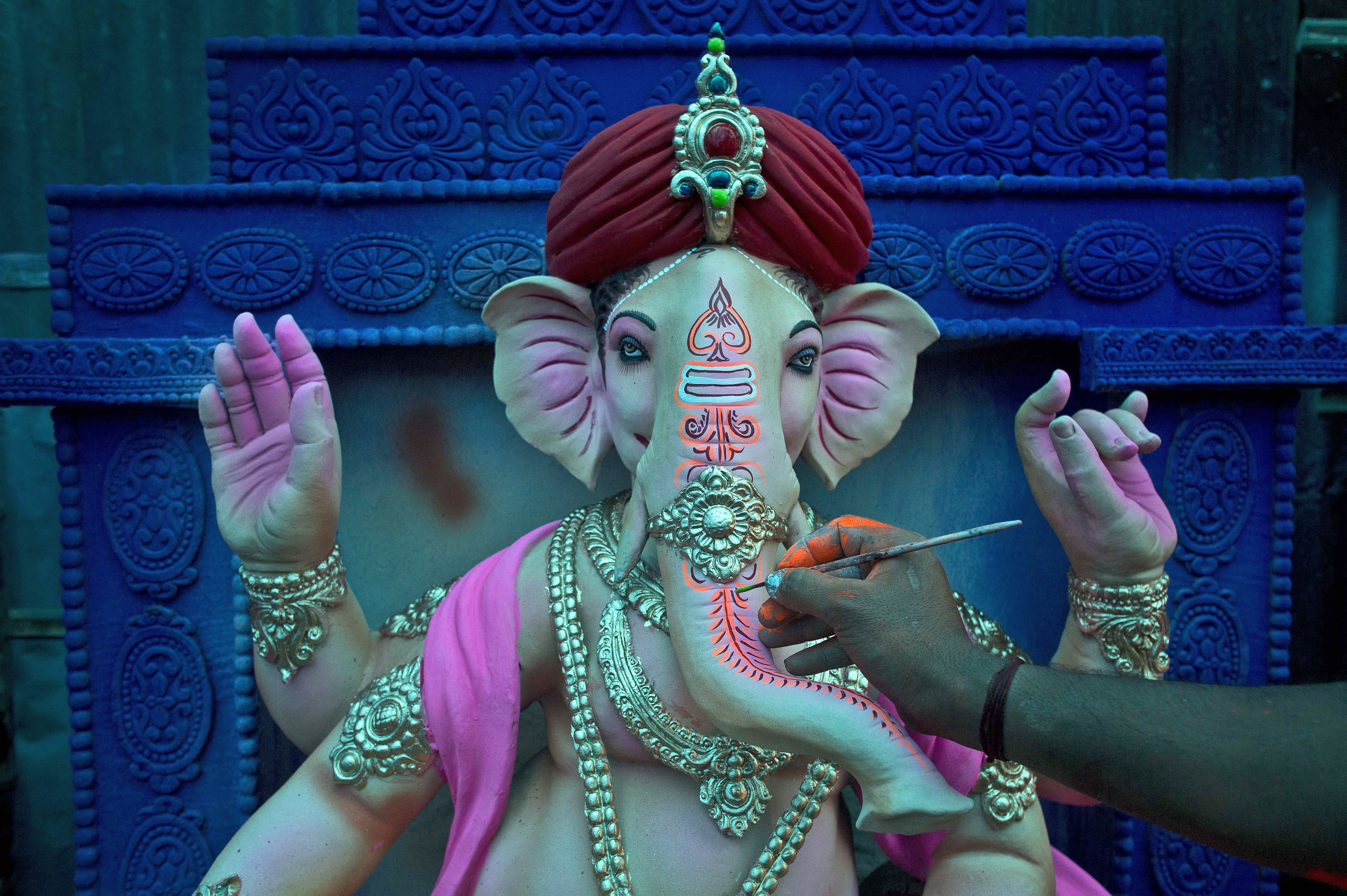 An artisan puts final touches on an idol of Hindu God Ganesha ahead of Ganesha Chaturthi at a workshop in Gauhati, India, Wednesday, Sept. 12, 2018. The ten-day long festival celebrating the birth of Ganesha begins Sept. 13. (AP Photo/Anupam Nath)