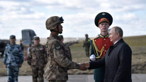 Russian President Vladimir Putin, right, shakes hands with a Chinese serviceman as he attends military exercises on training ground