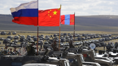 Russian, Chinese and Mongolian national flags set on armored vehicles develop in the wind during a military exercises on training ground