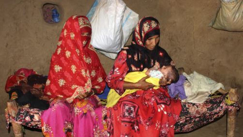 In this Sept. 22, 2018 photo, Amna Ali, right, mother of 3-year-old Zaifa Shouib, who was the fifth child known to have died in the district this year of malnutrition-related illness, sits in her hut holding a baby in Khayran al-Maharq, Hajjah, Yemen. At a local medical facility which did not have enough supplies, Zaifa's father was told she had to be taken to a hospital further away to treat kidney complications. He had no way to pay for transportation there. (AP Photo/Hammadi Issa)