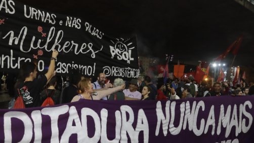 Demonstrators carry a banner that reads in Portuguese