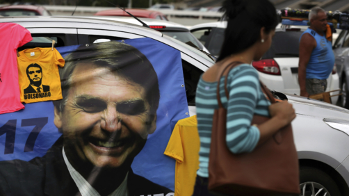 A supporter sells T-shirts with an image of right-wing presidential candidate Jair Bolsonaro, at a bus station in Brasília, Brazil, Wednesday, Oct. 17, 2018. Before the run-off election in Brazil on 28 October, right-wing populist presidential candidate Bolsonaro has a clear advantage over left-wing Workers' Party presidential candidate Fernando Haddad. (AP Photo/Eraldo Peres)