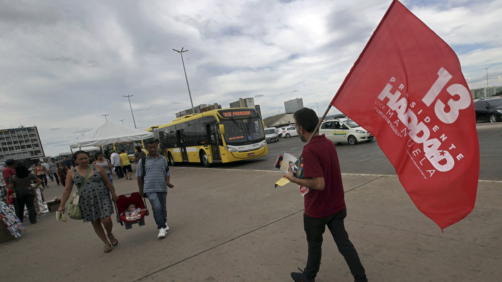 A lonely supporter of Workers' Party presidential candidate Fernando Haddad walks with a campaign flag, at a bus station in Brasília, Brazil, Wednesday, Oct. 17, 2018. Before the run-off election in Brazil on 28 October, right-wing populist presidential candidate Jair Bolsonaro is showing a clear advantage over Haddad. (AP Photo/Eraldo Peres)