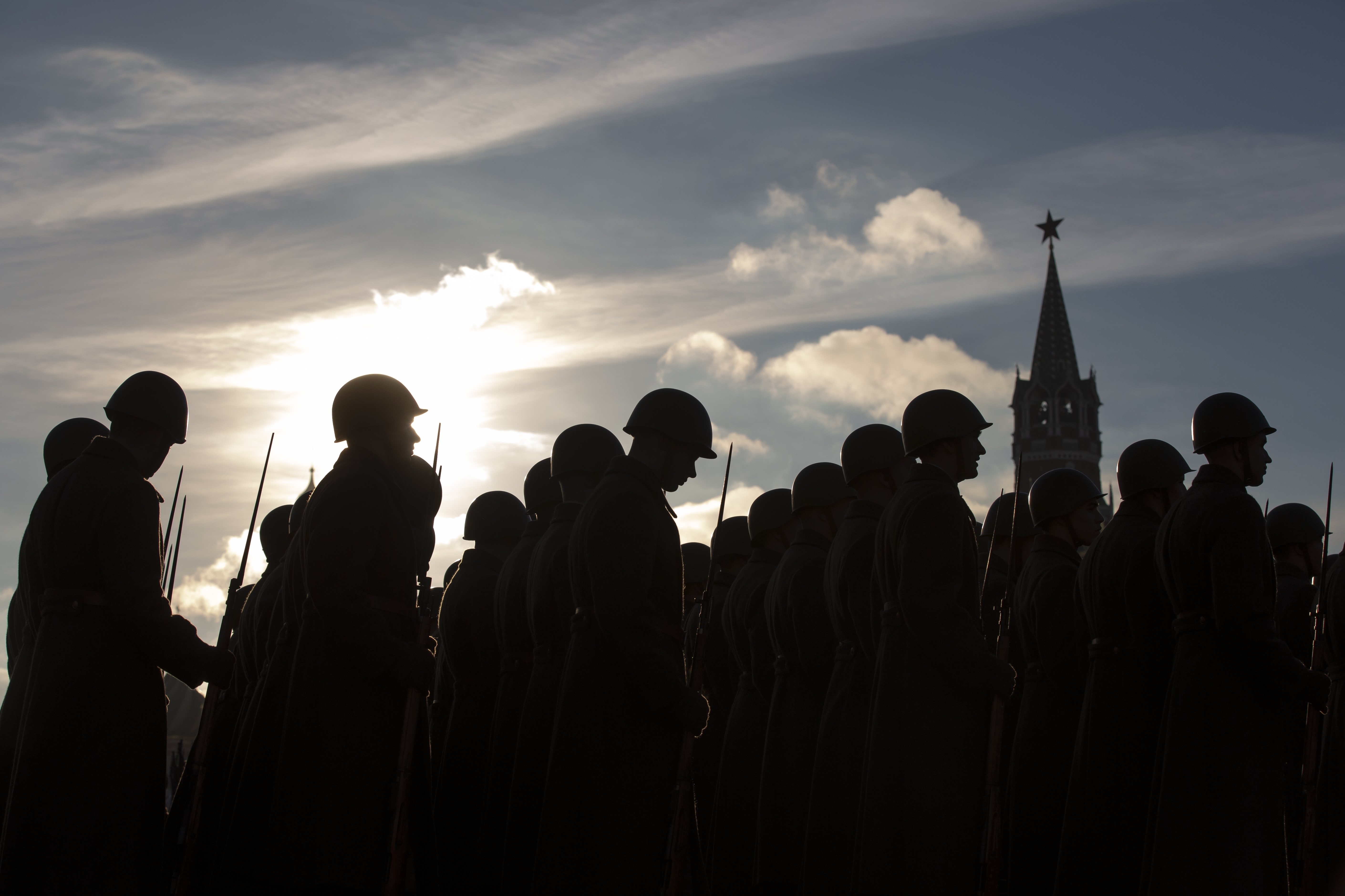 Russian soldiers dressed in Red Army World War II uniforms stand prior to the start of a rehearsal of the Nov. 7 parade in Red Square, with the Spasskaya Tower in the background, in Moscow, Russia, Monday, Nov. 5, 2018. The parade marks the 77th anniversary of a World War II historic parade in Red Square and honored the participants in the Nov. 7, 1941 parade who headed directly to the front lines to defend Moscow from the Nazi forces. (AP Photo/Alexander Zemlianichenko)