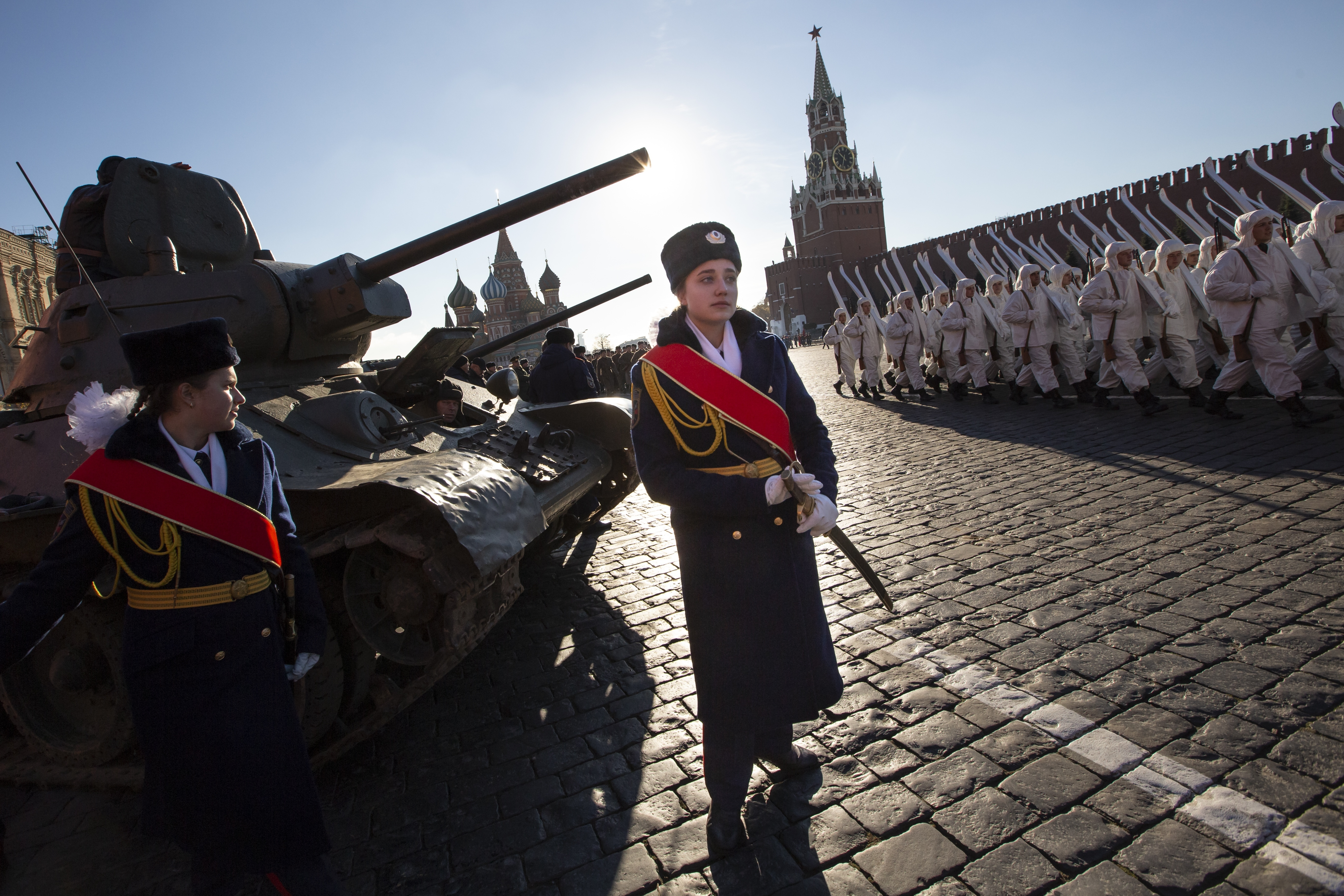 A Russian cadet stands in front of a legendary Soviet tank T-34 as other soldiers dressed in Red Army World War II uniforms march during a rehearsal of the Nov. 7 parade in Red Square, with St. Basil Cathedral and the Spasskaya Tower in the background, in Moscow, Russia, Monday, Nov. 5, 2018. The parade marks the 77th anniversary of a World War II historic parade in Red Square and honored the participants in the Nov. 7, 1941 parade who headed directly to the front lines to defend Moscow from the Nazi forces. (AP Photo/Alexander Zemlianichenko)
