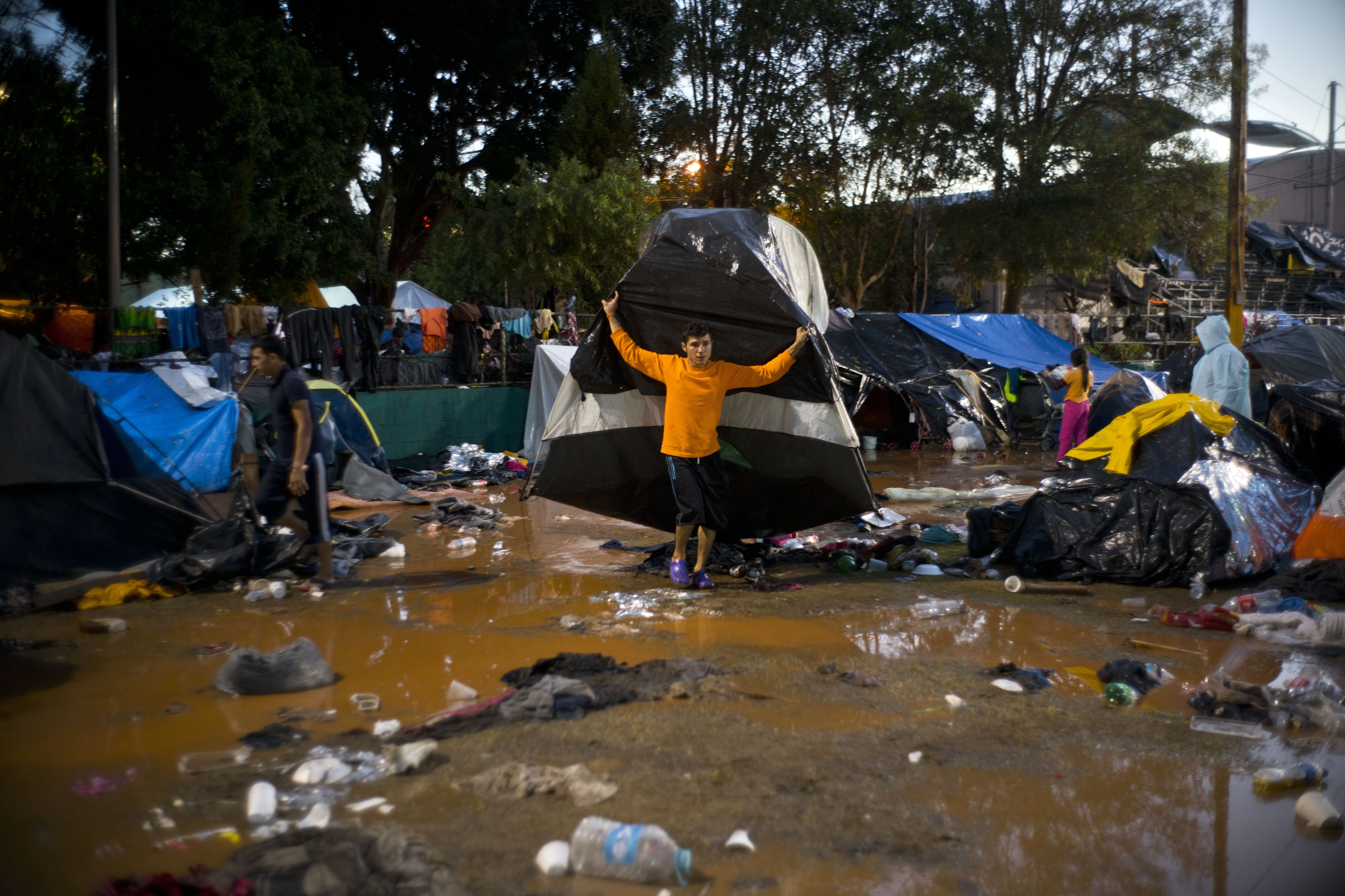 A migrant moves his tent in the rain before he was being transferred by bus to another shelter in better conditions than the flooded sports complex where thousands of Central Americans were living, in Tijuana, Mexico, following heavy rains, on Thursday, Nov. 29, 2018. Aid workers and humanitarian organizations expressed concerns Thursday about the unsanitary conditions at the sports complex in Tijuana where more than 6,000 Central American migrants are packed into a space adequate for half that many people and where lice infestations and respiratory infections are rampant. (AP Photo/Ramon Espinosa)