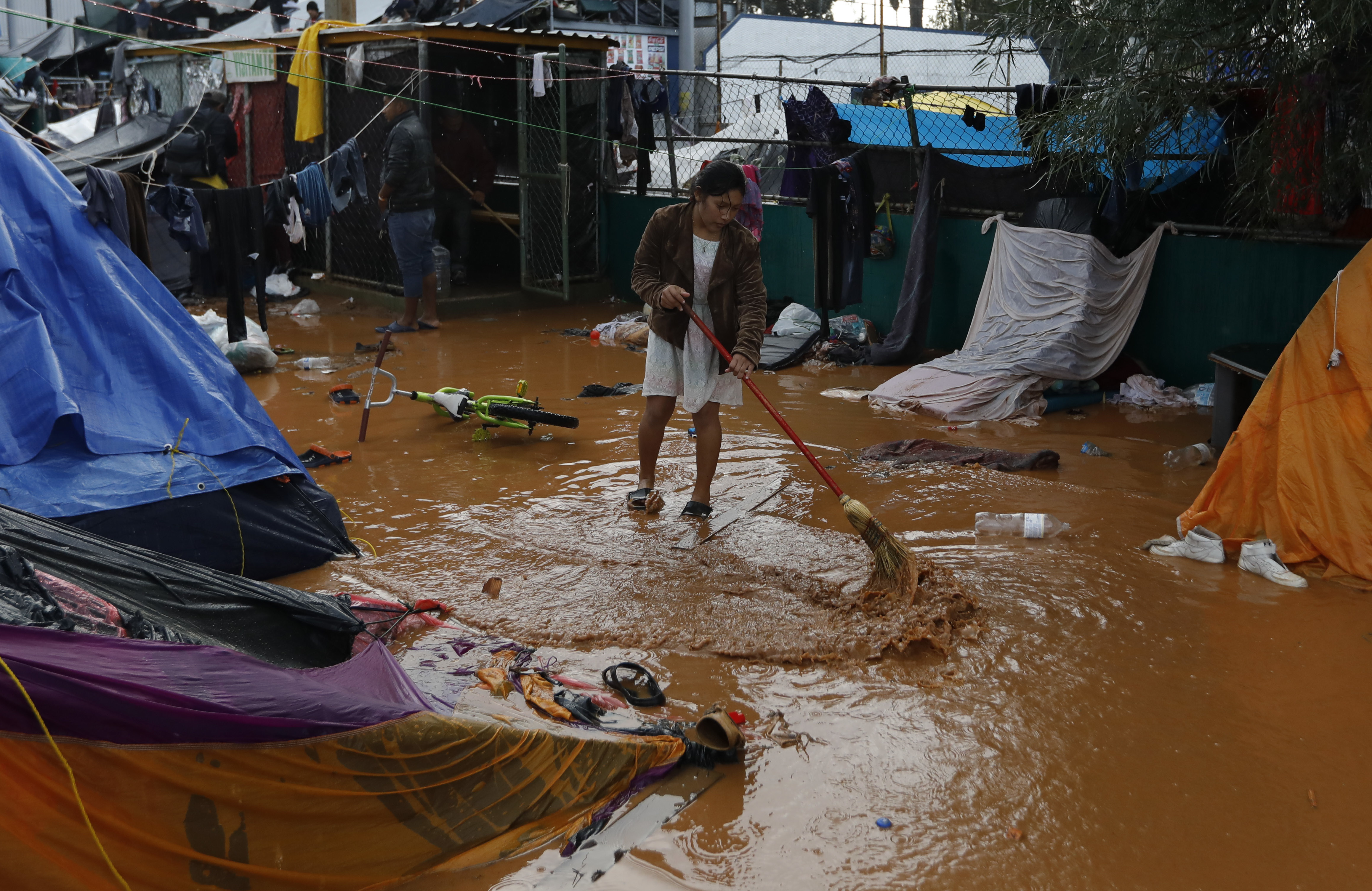 A woman attempts to sweep away flood waters, between bouts of heavy rain at a sports complex sheltering thousands of Central Americans in Tijuana, Mexico, Thursday, Nov. 29, 2018. Aid workers and humanitarian organizations expressed concerns Thursday about the unsanitary conditions at the sports complex in Tijuana where more than 6,000 Central American migrants are packed into a space adequate for half that many people and where lice infestations and respiratory infections are rampant.(AP Photo/Rebecca Blackwell)