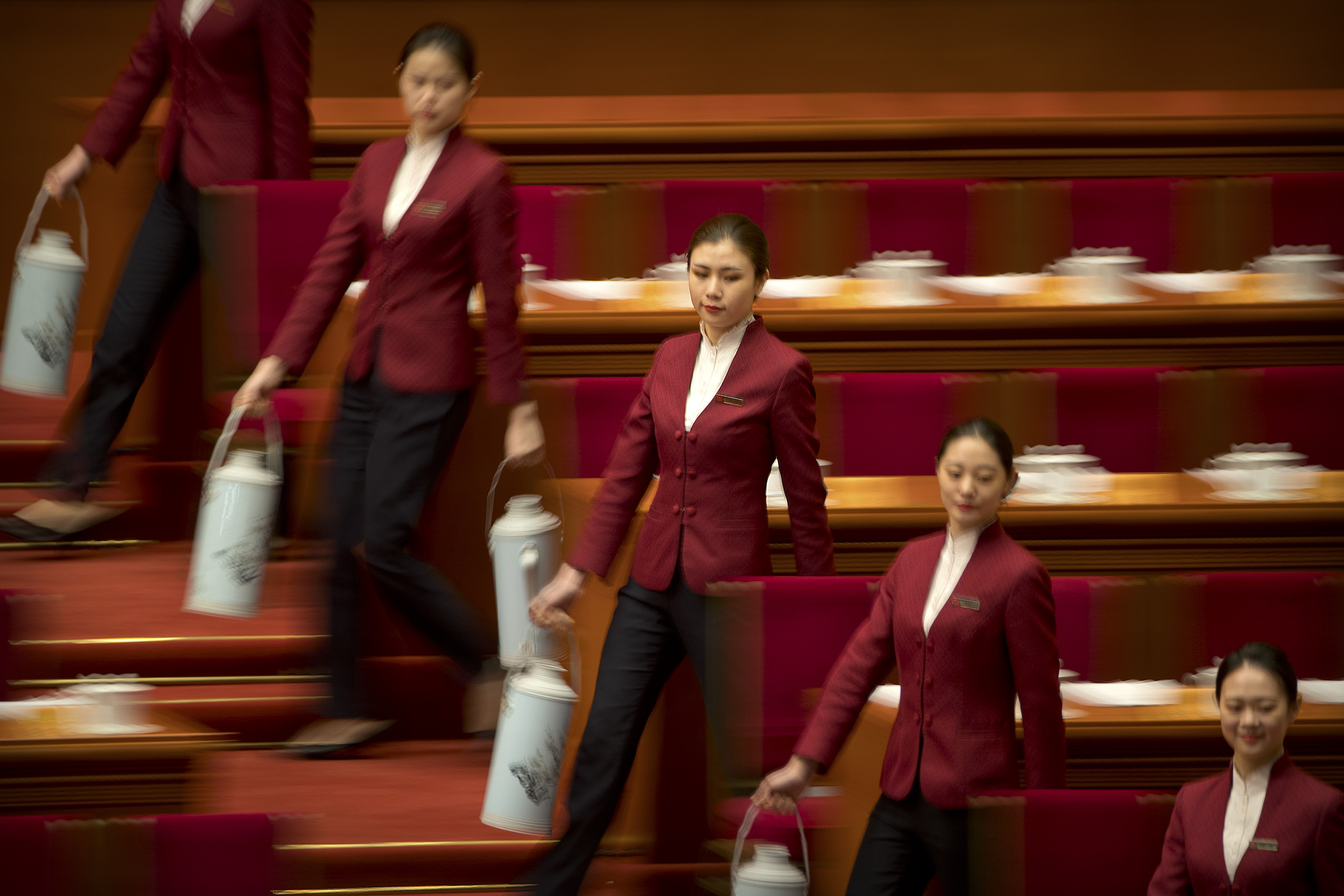 Hostesses carry flasks of water to fill teacups for delegates before the closing session of the Chinese People's Political Consultative Conference (CPPCC) at the Great Hall of the People in Beijing, Wednesday, March 13, 2019. (AP Photo/Mark Schiefelbein)