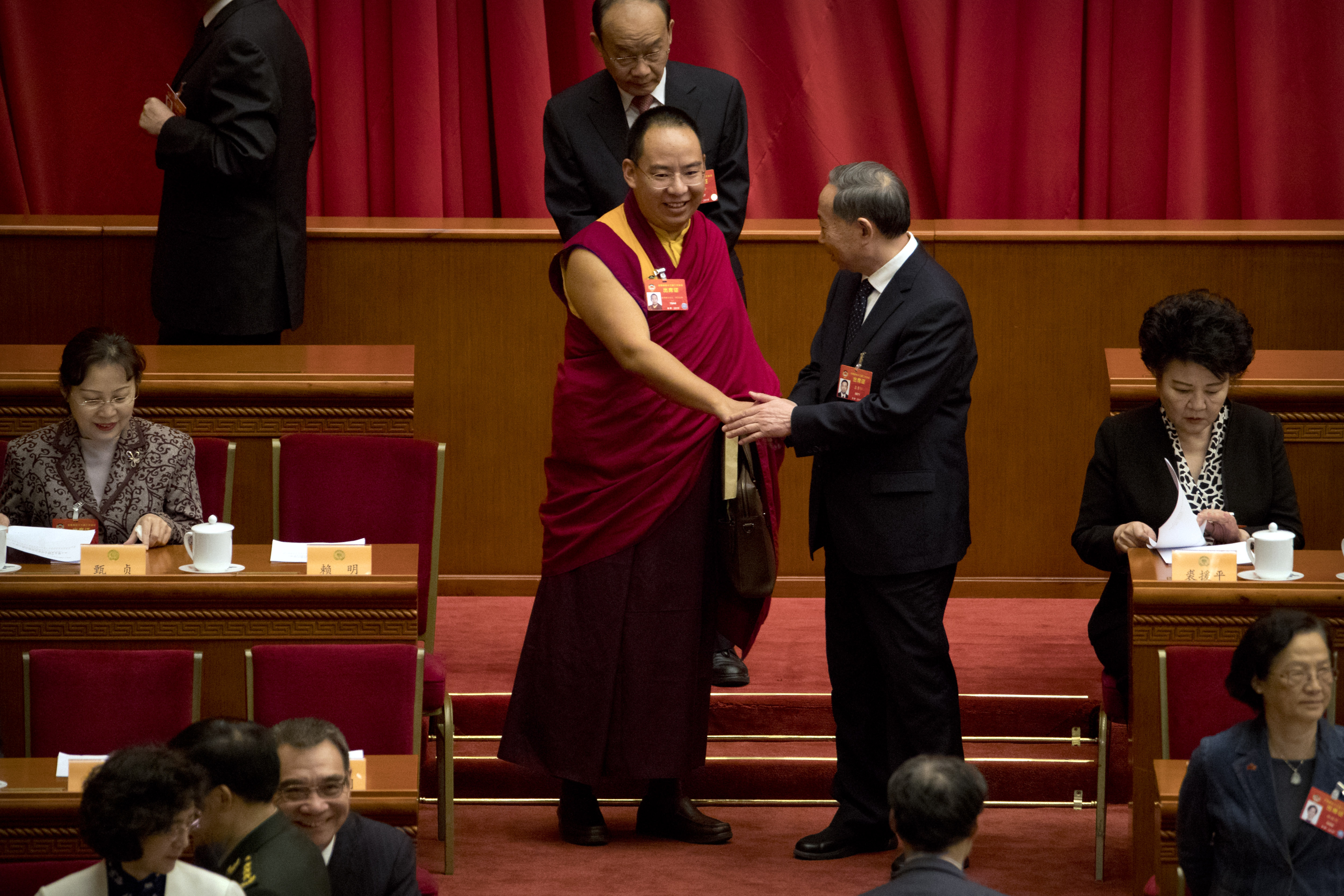 The 11th Panchen Lama Bainqen Erdini Qoigyijabu, a member of the National Committee of the Chinese People's Political Consultative Conference (CPPCC), is greeted as he arrives for the closing session of the CPPCC at the Great Hall of the People in Beijing, Wednesday, March 13, 2019. (AP Photo/Mark Schiefelbein)