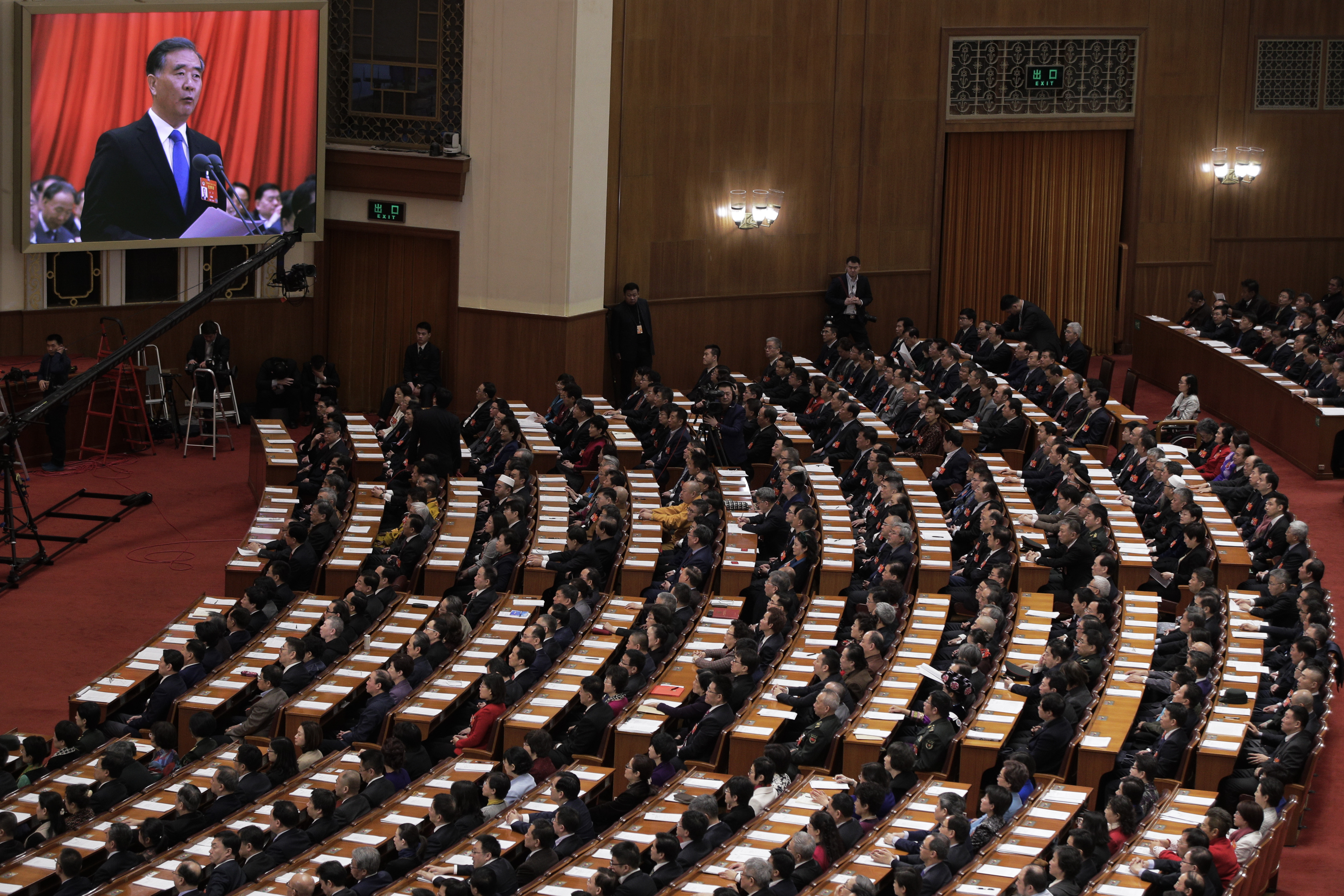 Chinese People's Political Consultative Conference (CPPCC) chairman and Politburo Standing Committee member Wang Yang appears on a screen delivers a closing speech for the Chinese People's Political Consultative Conference (CPPCC) at the Great Hall of the People in Beijing, Wednesday, March 13, 2019. (AP Photo/Andy Wong)