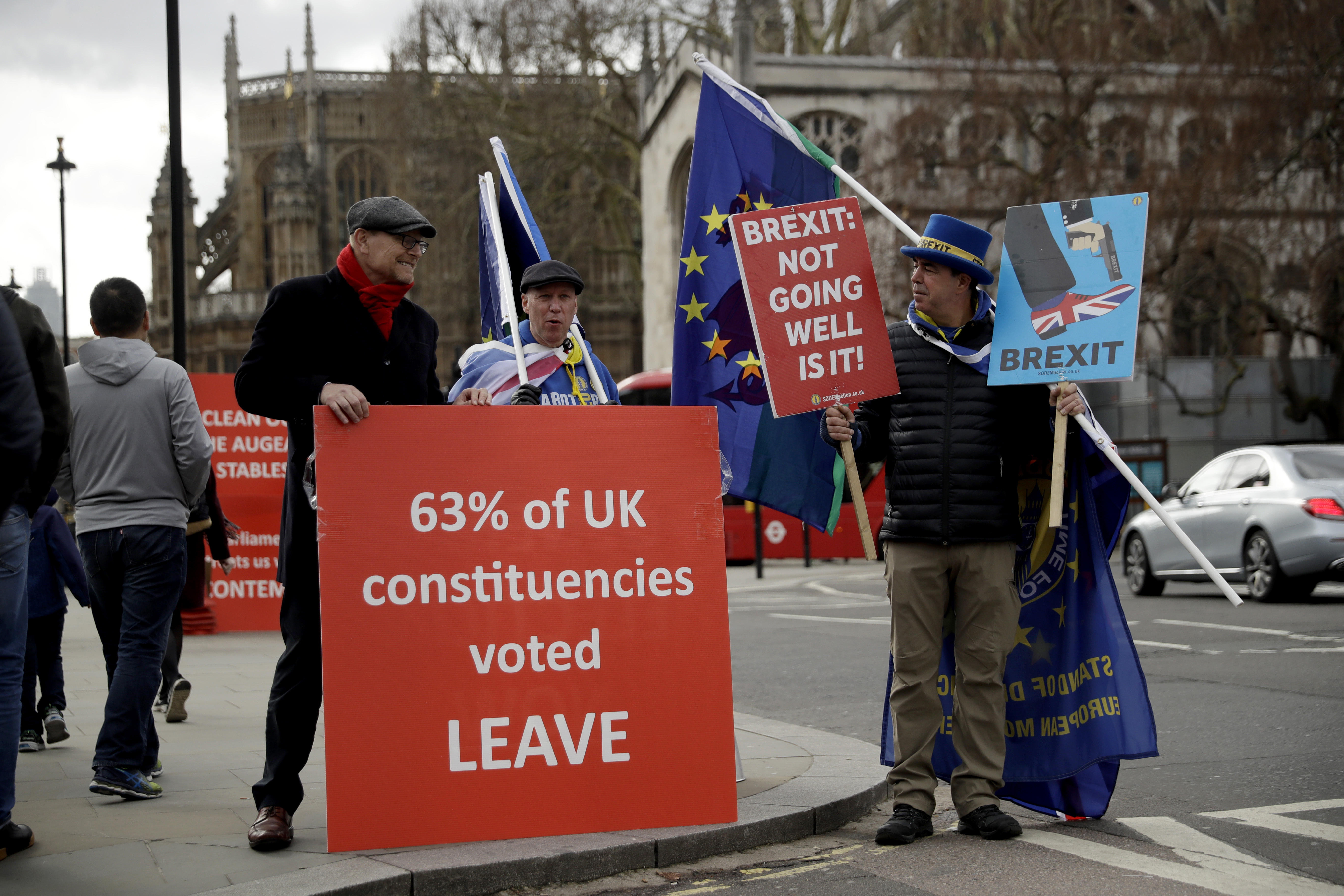 A pro-Brexit supporter, at left, protests next to anti-Brexit supporters protesting outside the Houses of Parliament in London, Monday, March 18, 2019. British Prime Minister Theresa May was making a last-minute push Monday to win support for her European Union divorce deal, warning opponents that failure to approve it would mean a long — and possibly indefinite — delay to Brexit. Parliament has rejected the agreement twice, but May aims to try a third time this week if she can persuade enough lawmakers to change their minds. (AP Photo/Matt Dunham)