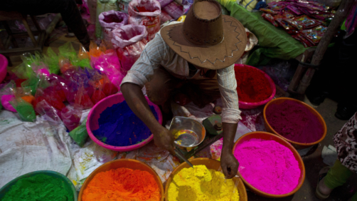 An Indian street vendor sells colored powder a day ahead of Holi, the festival of colors, in Gauhati, India, Wednesday, March 20, 2019. Holi also marks the advent of Spring season. (AP Photo/Anupam Nath)