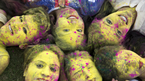 In this Wednesday, March 20, 2019 photo, Indian girls, faces smeared with color, pose for a photograph during Holi festival celebrations in Allahabad, India. The Hindu festival of colors also marks the advent of spring. (AP Photo/Rajesh Kumar Singh)